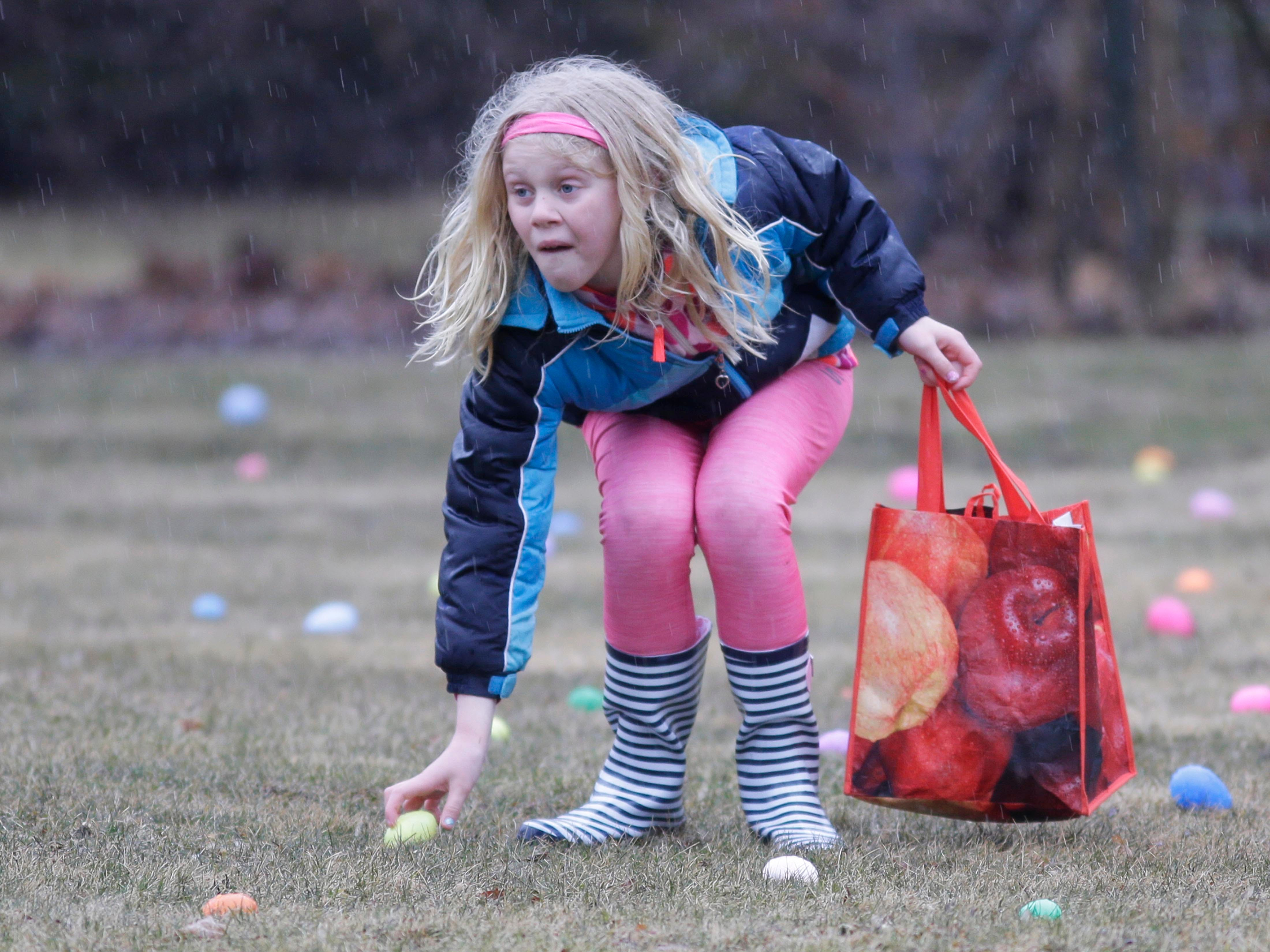 Fephra Martni, 7, picks up Easter Eggs at the Hocevar Family Easter Egg Hunt, Saturday, March 31, 2018, in Sheboygan Falls, Wis.
