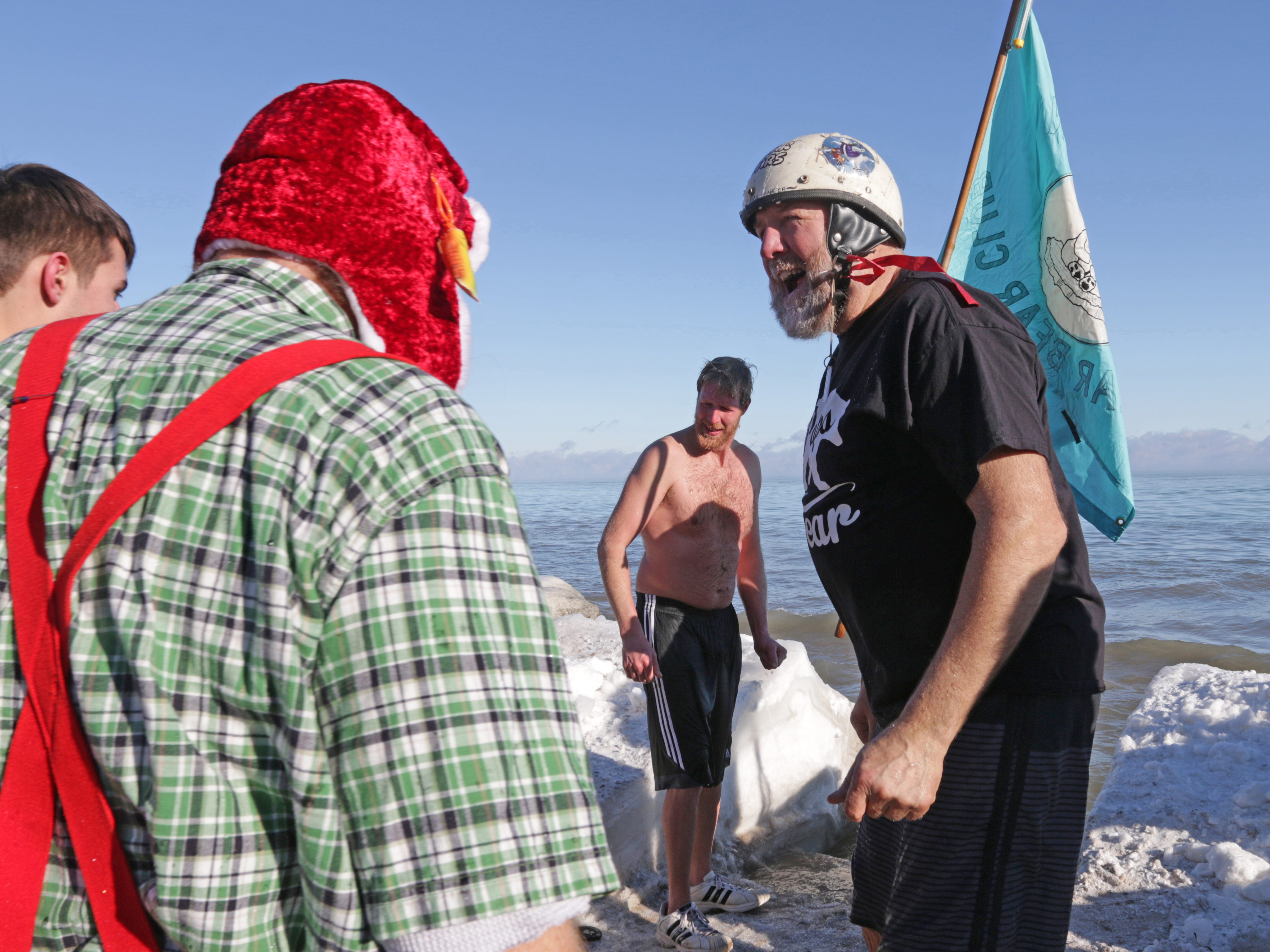 Justin Bohn, center, and his dad Arthur, right, take in Lake Michigan during the annual Polar Bear dip, Monday, January 1, 2018, in Sheboygan, Wis.