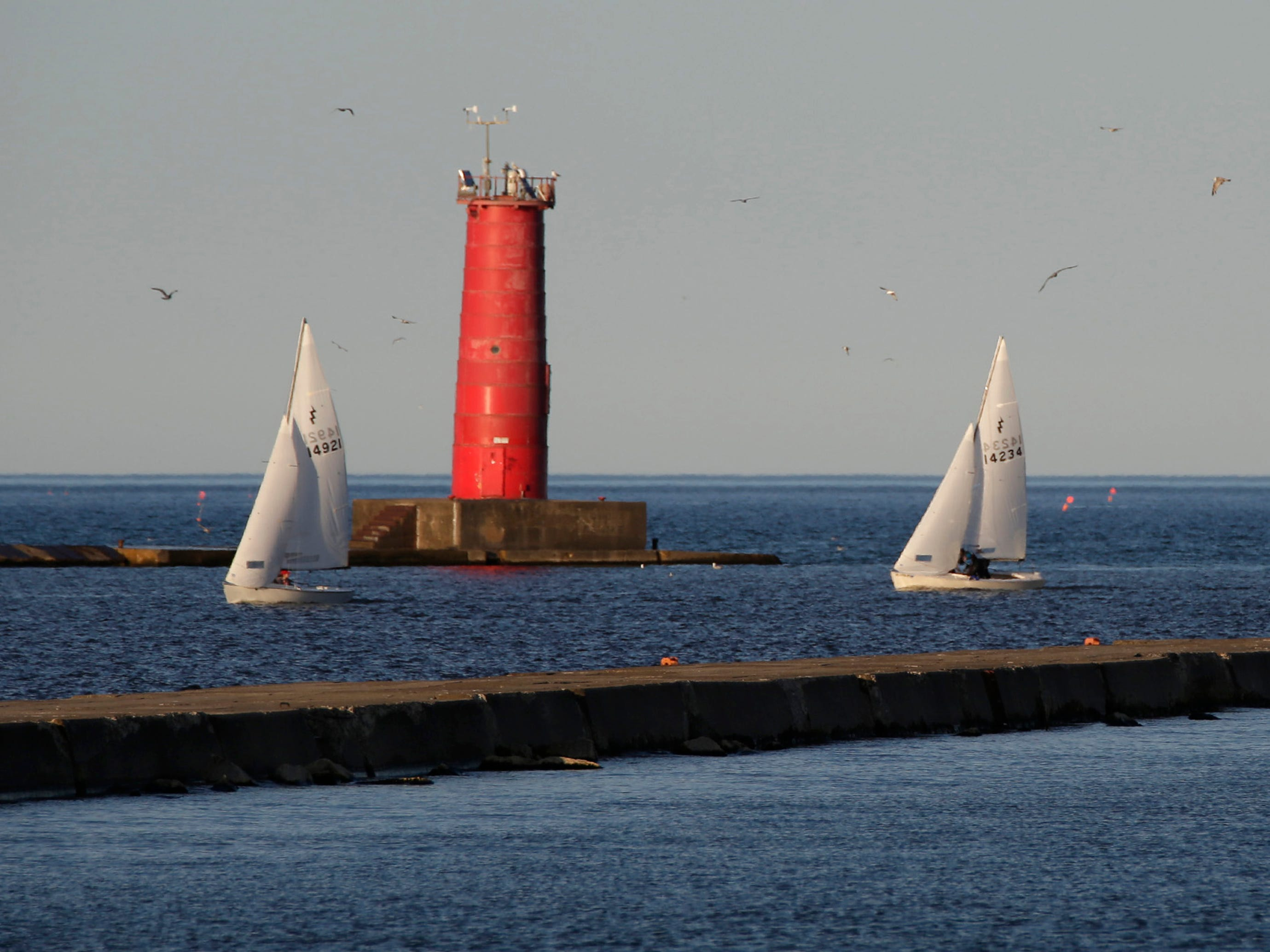 A trio of sailboats arrive near the Sheboygan lighthouse, Tuesday, June5, 2018, in Sheboygan, Wis.