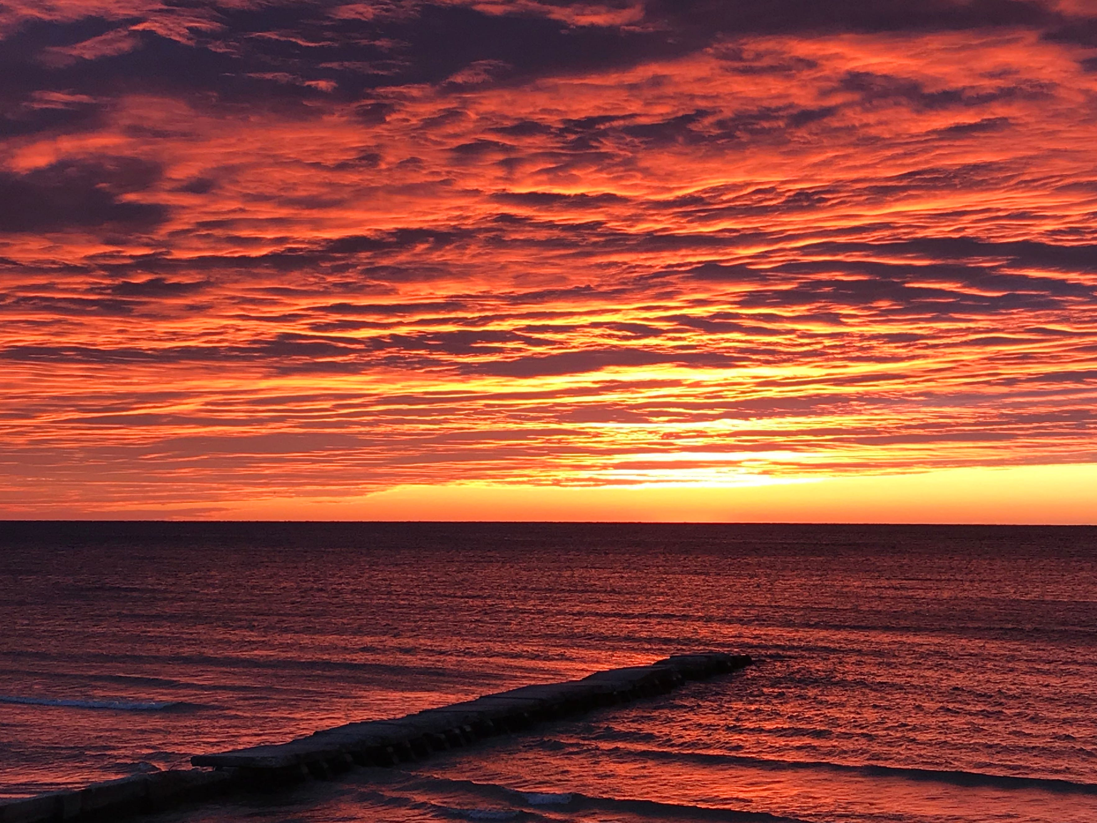 Clouds glow with morning light as a jetty juts out to Lake Michigan along Broughton Drive, Tuesday, October 16, 2018, in Sheboygan, Wis.