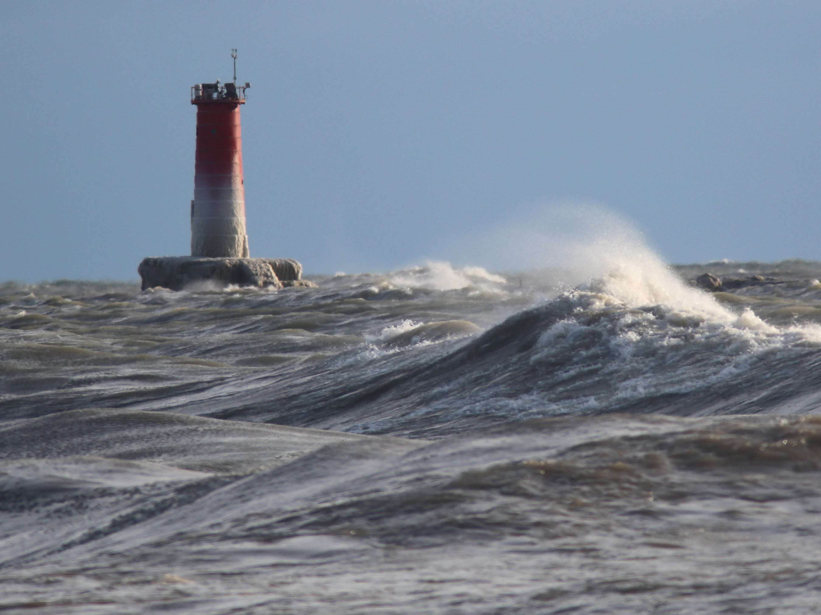 Whitecaps spray water near the Sheboygan lighthouse, Friday, January 12, 2018, in Sheboygan, Wis.