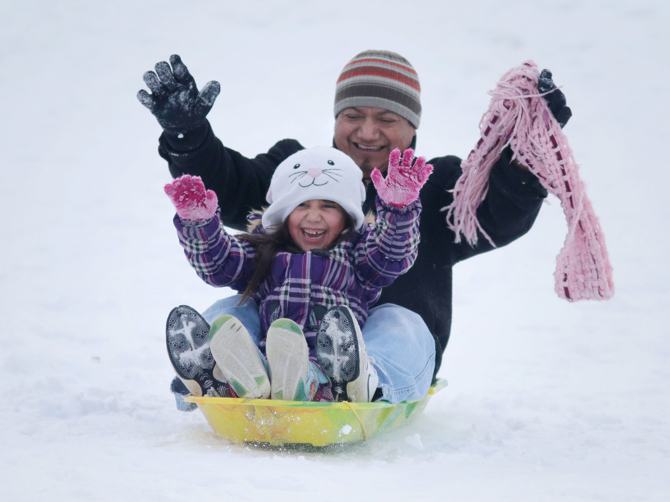 Geno Ramos, of Sheboygan, enjoys a ride down the Kiwanis Park sledding hill with his daughter Dalia, 5, Saturday, February 10, 2018, in Sheboygan, Wis.