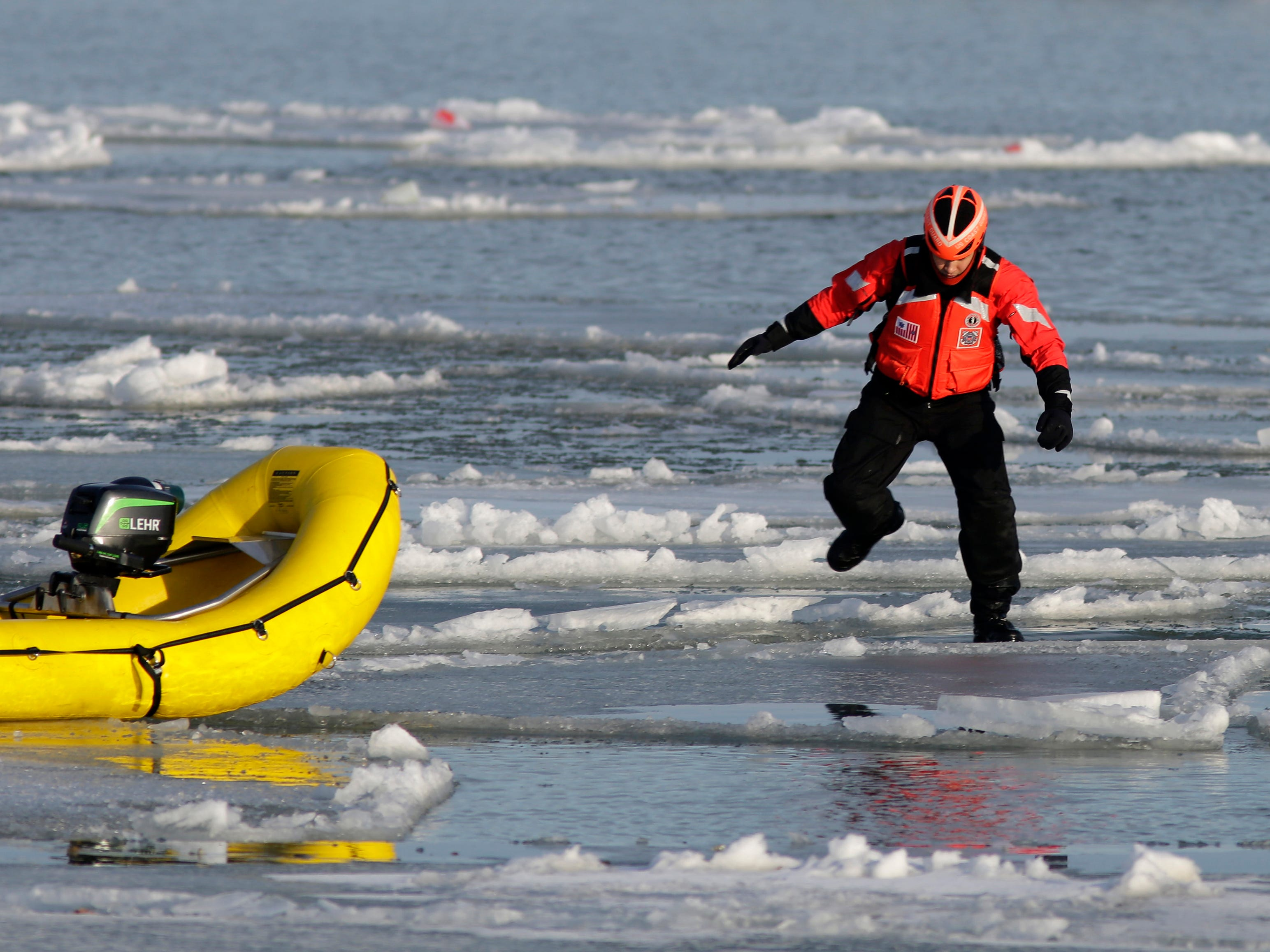 A U.S. Coast Guard member leaps on the broken ice during ice rescue training, Tuesday, January 9, 2018, at Sheboygan, Wis. The Guard trains each winter to certify their skills in ice rescue.
