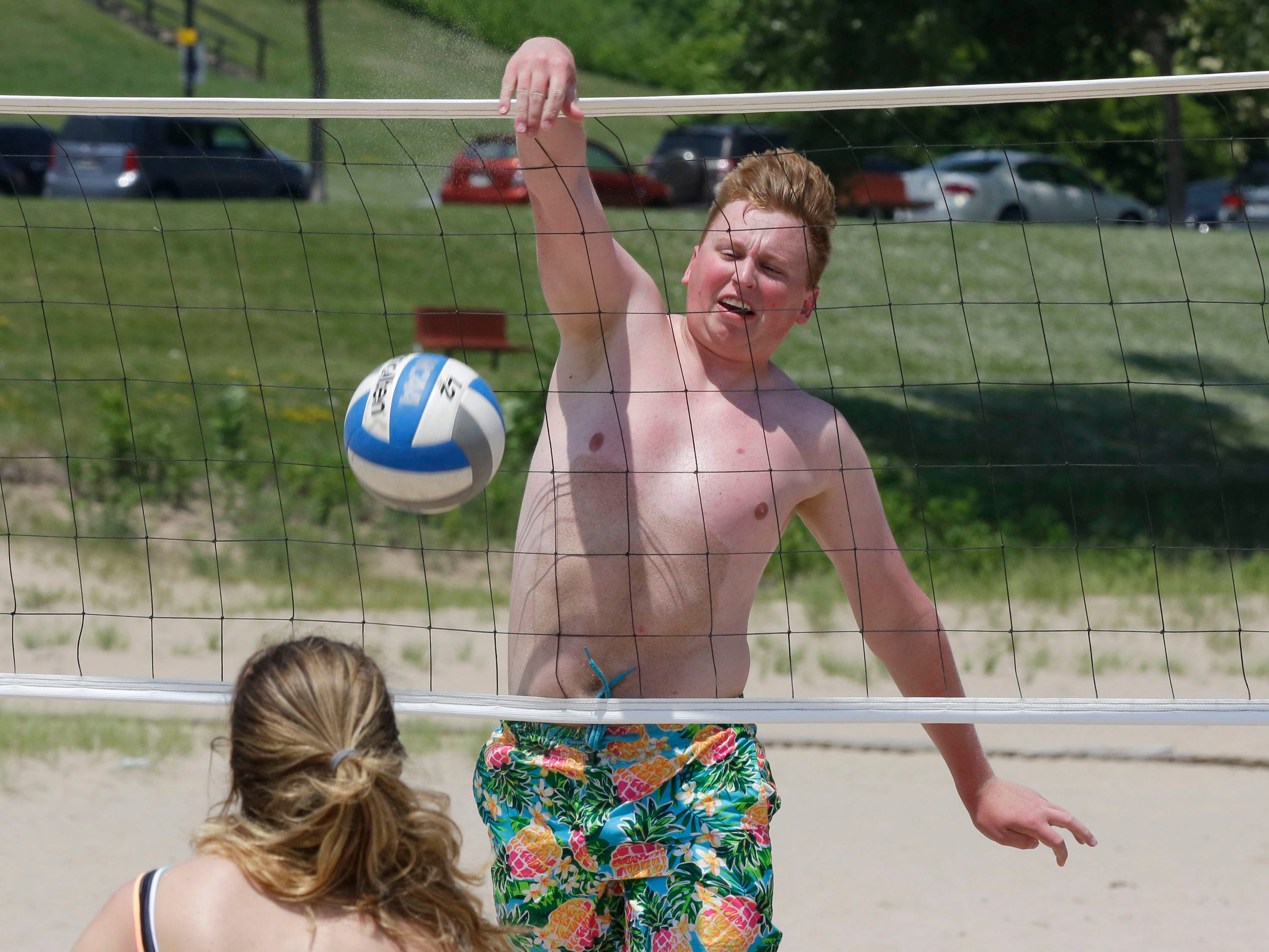 Max Brink of Wausau, Wis. spikes the ball by Rebecca Oliver of Sheboygan during a pickup volleyball game at Deland Park, Saturday June 30, 2018, in Sheboygan, Wis.