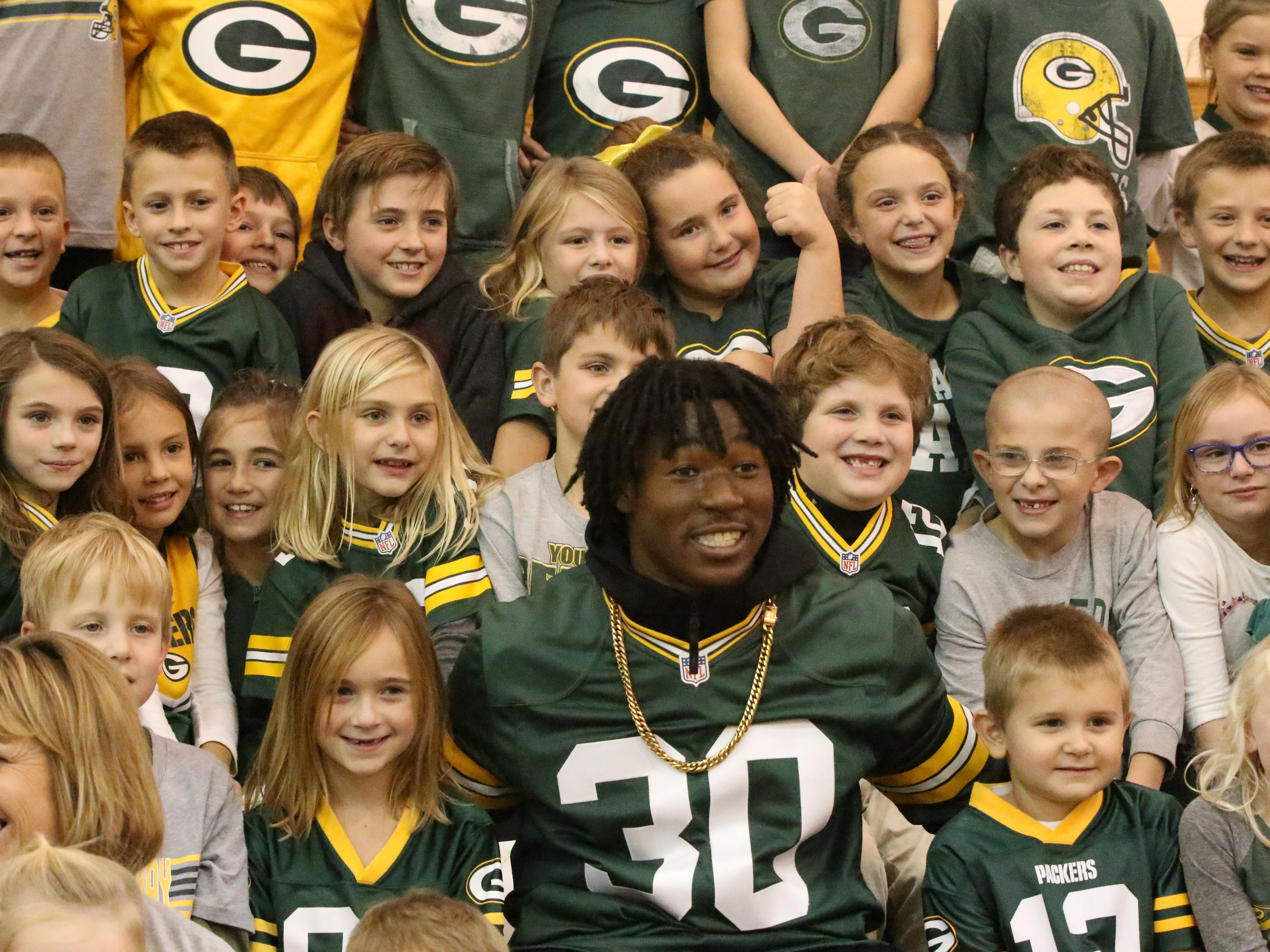 Green Bay Packer Jamaal Williams smiles with student from Plymouth's St. John the Baptist Catholic School, Tuesday, November 6, 2018, in Plymouth, Wis.