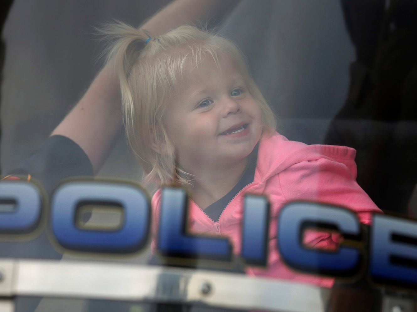 Emma Bastil,2, of Sheboygan, smiles while sitting on a police motorcycle during National Night Out at End Park, Tuesday, August 7, 2018, in Sheboygan, Wis. National Night Out is a community-police awareness-raising event.