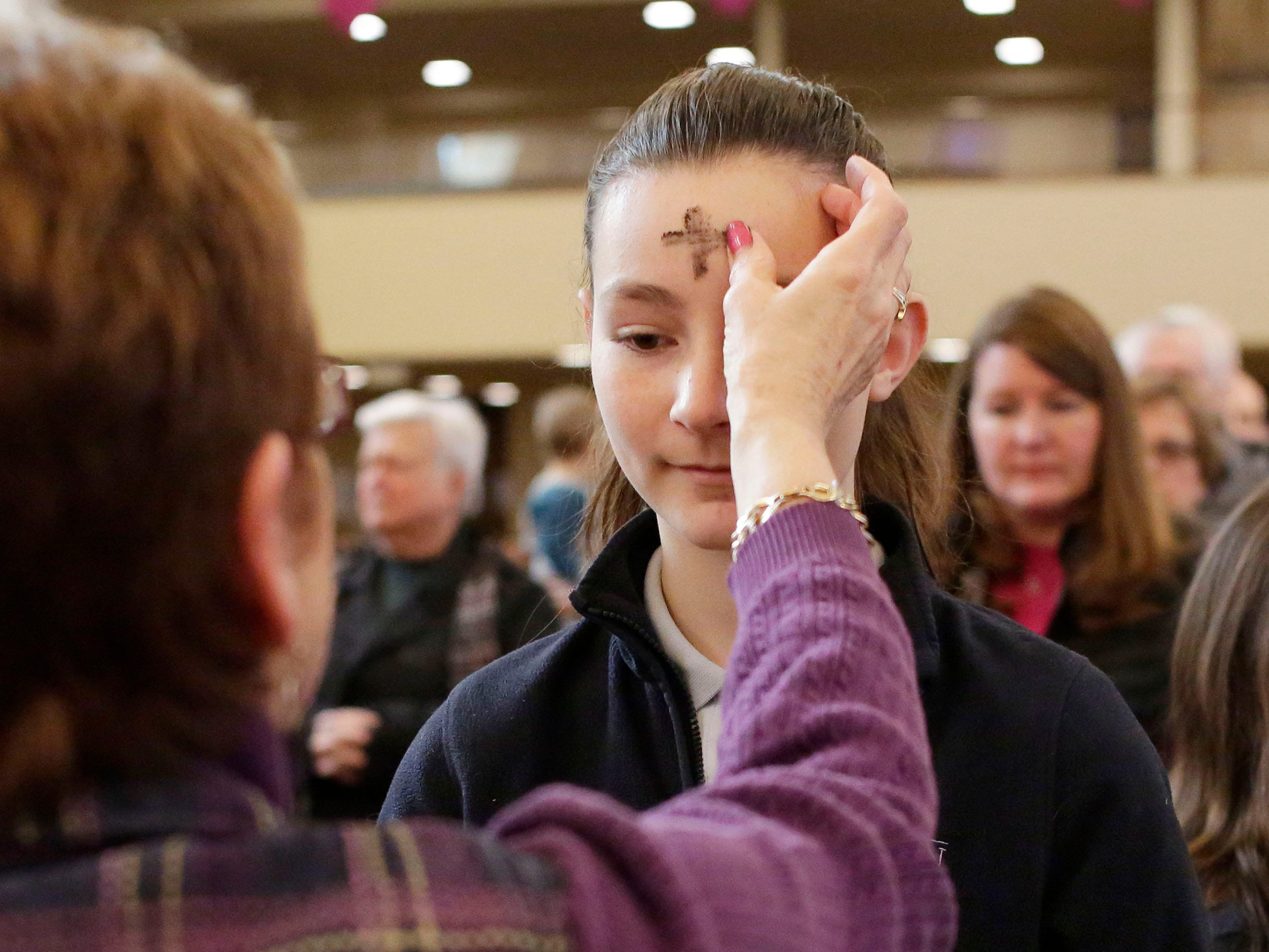 St. Elizabeth Ann Seton Catholic School student Eileen English receives ashes at Holy Name Catholic Church Wednesday, February 14, 2018, in Sheboygan, Wis.