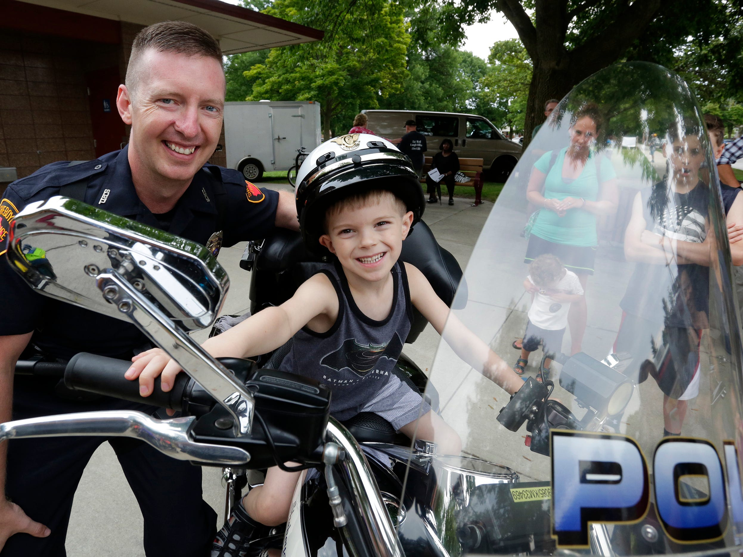 Sheboygan Police Department Motorcycle officer Dustin Fickett, left, smiles with Brady Stelter, during National Night Out at End Park, Tuesday, August 7, 2018, in Sheboygan, Wis. National Night Out is a community-police awareness-raising event.