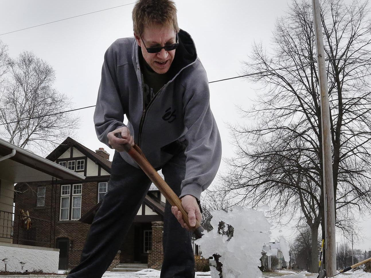 Mark Rieger of Sheboygan shovels ice off his sidewalks near his North 3rd Street home, Thursday, January 25, 2018, in Sheboygan, Wis.
