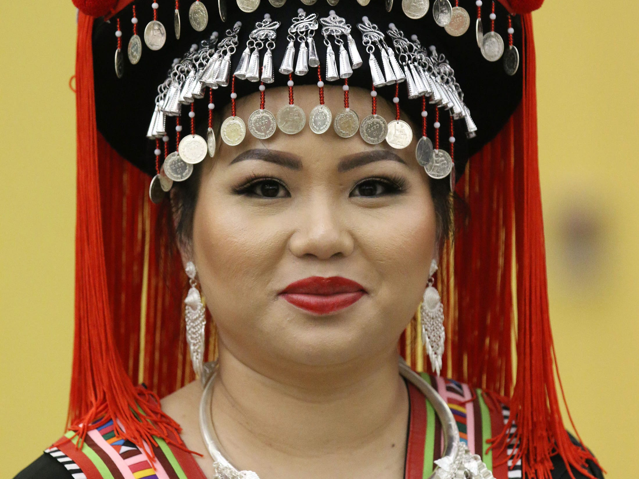 Tina Chang of Sheboygan, poses with her traditional Hmong costume, Friday, November 23, 2018, in Sheboygan, Wis. She was at the Hmong New Year celebration which is being held at Sheboygan North High School this weekend.