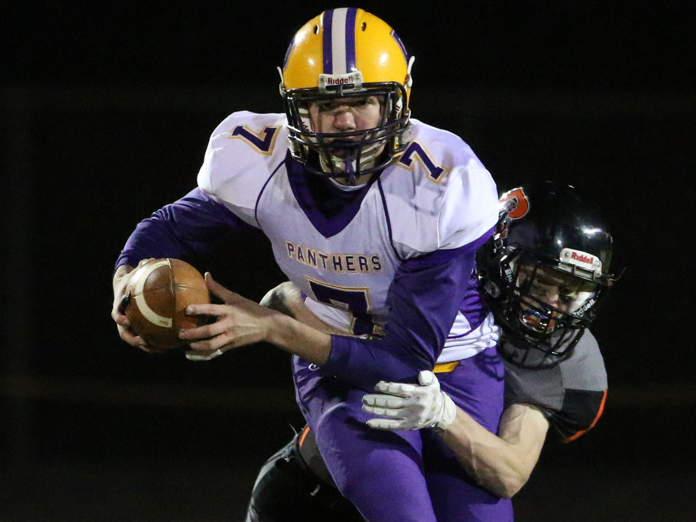 Pittsville's Matthew Kissner (7) is pulled down by a Reedsville player, Friday, November 2, 2018, in Reedsville, Wis.