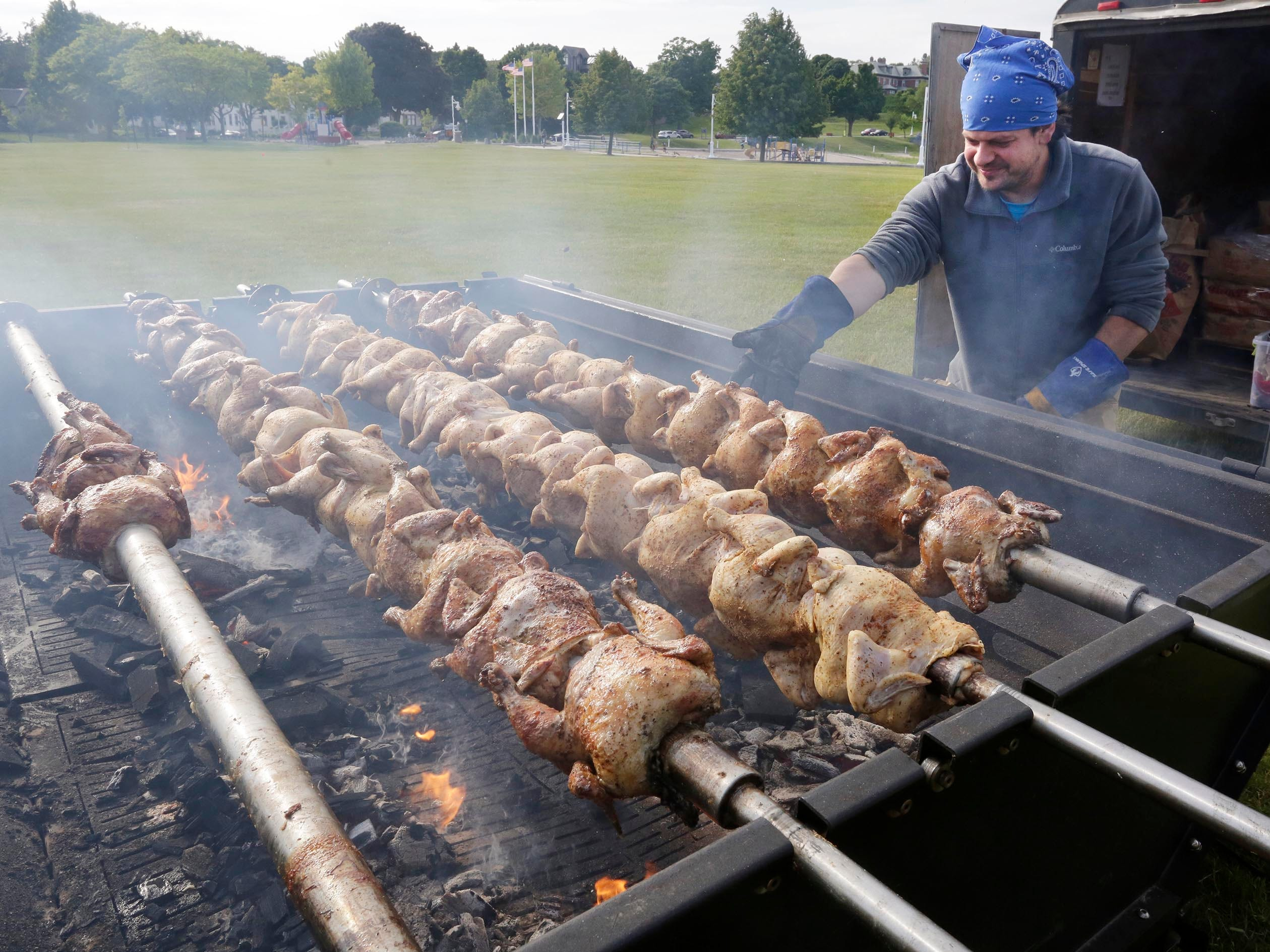Stavros Bhronis of Sheboygan add charcoal to the grill during the 75th Annual Greek Festival, Friday, June 22, 2018, in Sheboygan, Wis.