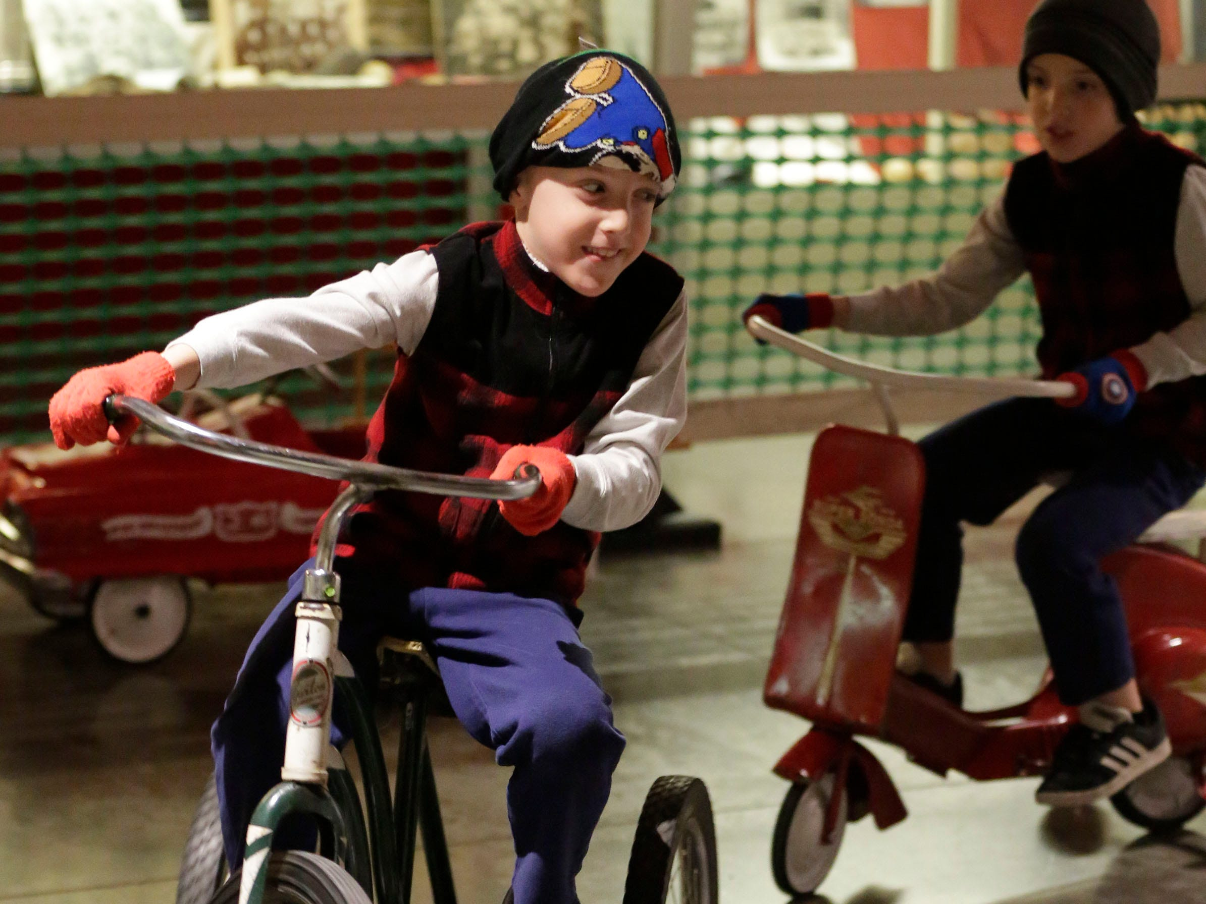 Bryce Van Auken, 7, of Sheboygan Falls, Wis., pedals a vintage Garton toy ahead of his twin brother Nolan, 7, during the Sheboygan County Historical Museum's Holiday Memories, Friday, November 23, 2018, in Sheboygan, Wis.