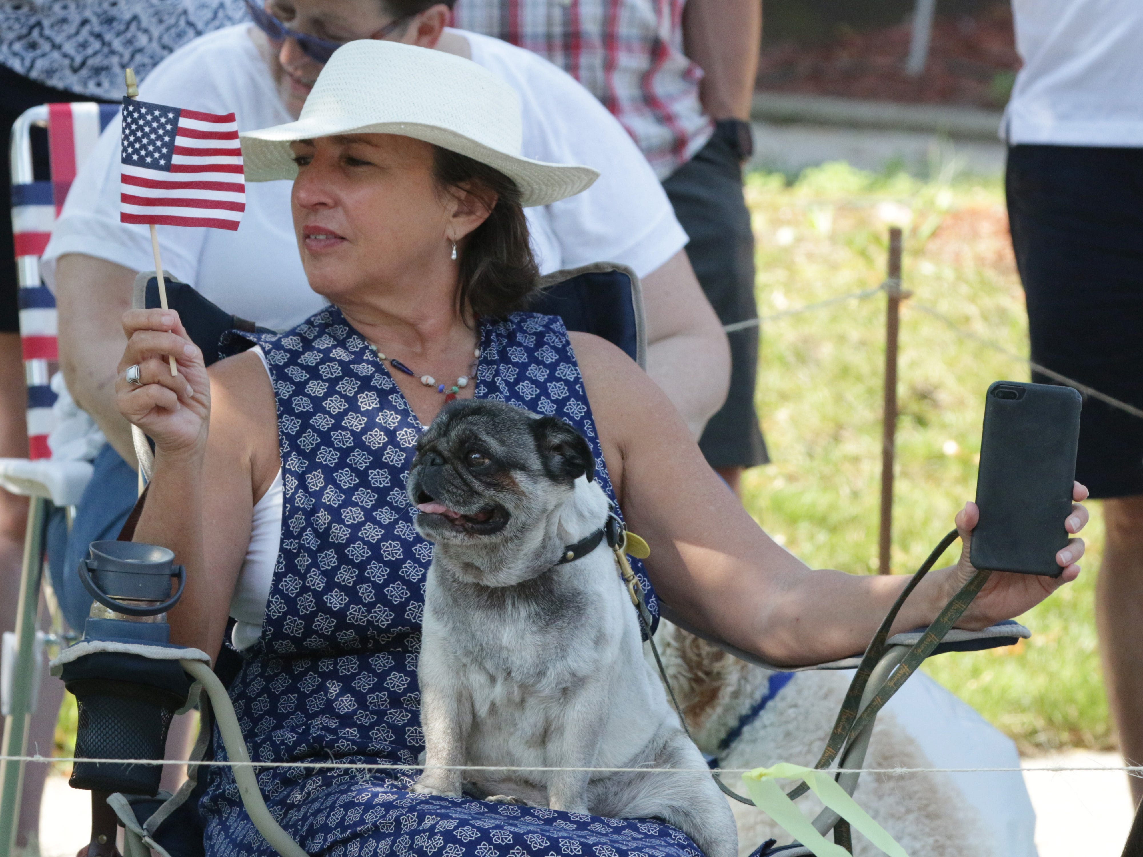 Ellen O'Brien of Elkhart Lake, Wis. and her dog Mr. Magoo watch the Fourth of July Parade, Wednesday, July 4, 2018, in Sheboygan, Wis.
