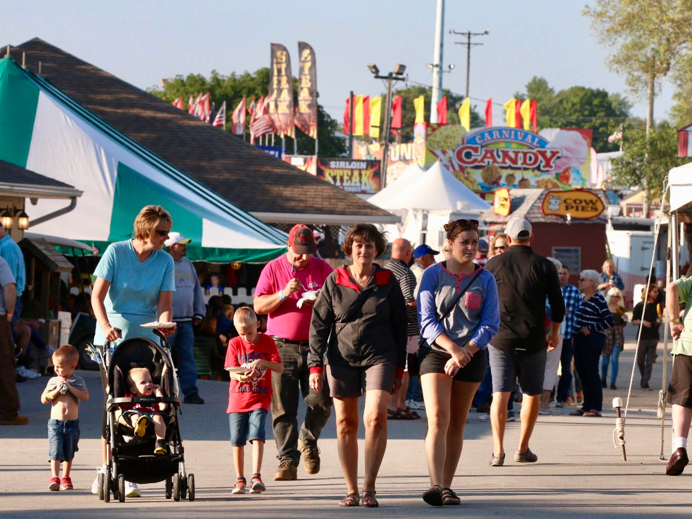 People crowd the midway at the Sheboygan County Fair, Thursday, August 30, 2018, in Plymouth, Wis.