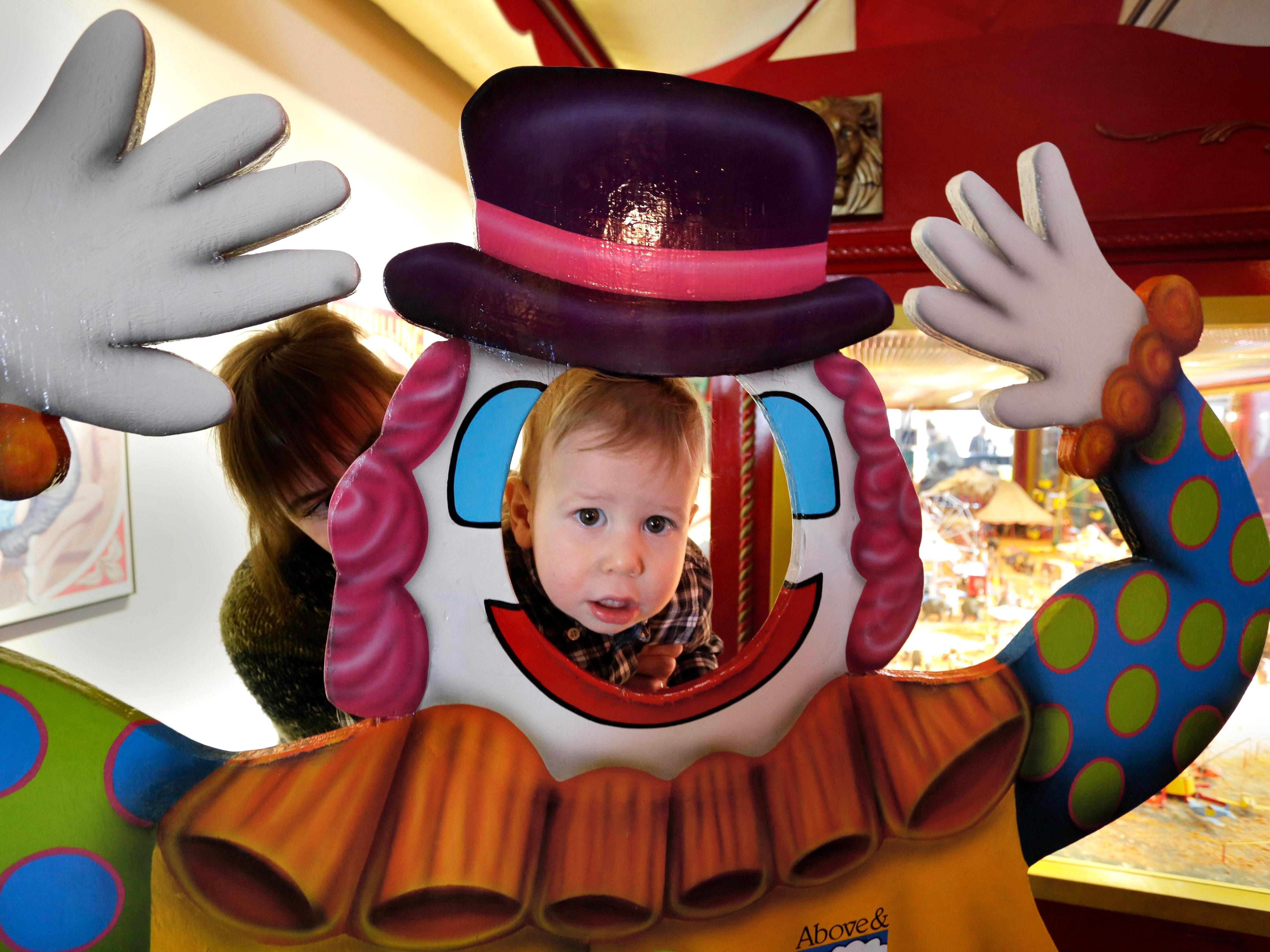Thomas Lampe, 1, peers through a clown cutout at the Above and Beyond Children's Museum during Facepaint Friday, Friday, January 19, 2018 in Sheboygan, Wis.