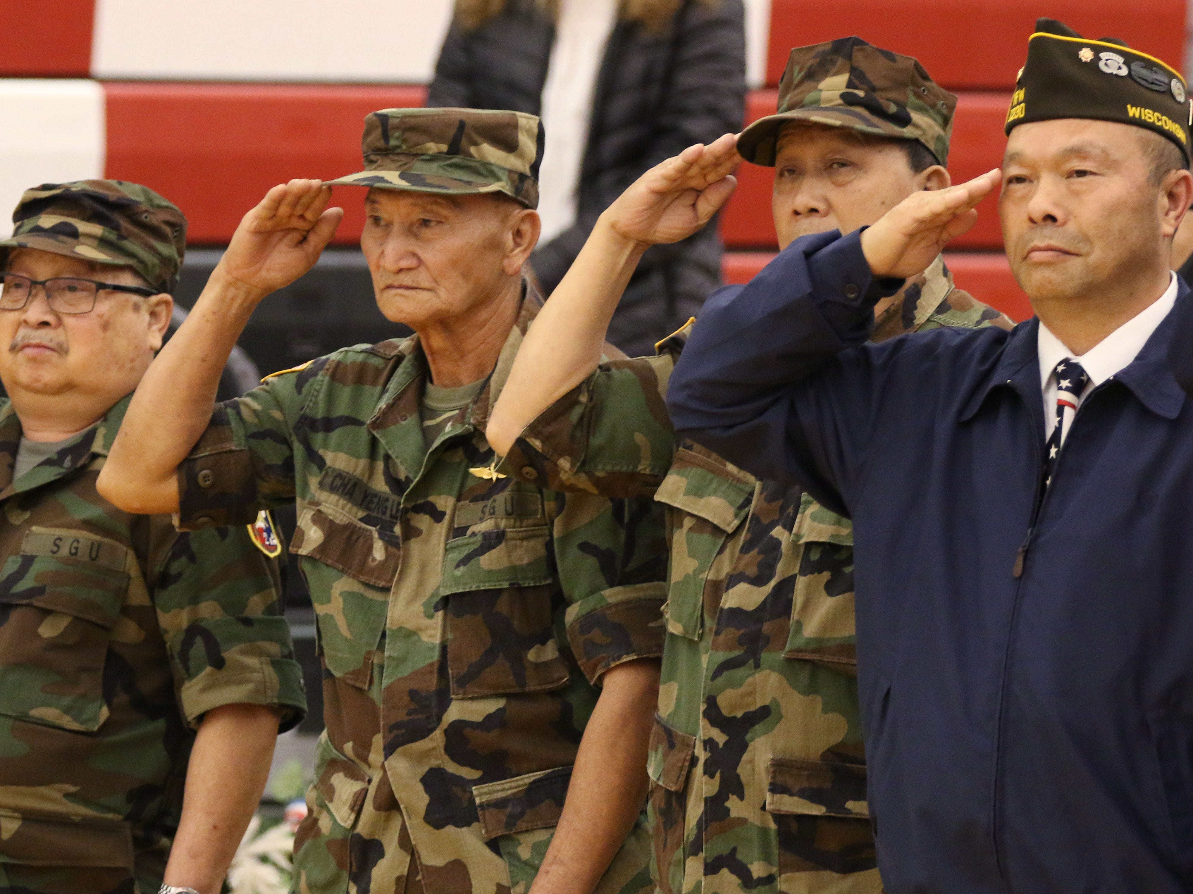 Hmong veterans salute the flag during the playing of the national anthem during the Veterans Day Program held at Sheboygan South High School, Friday, November 9, 2018, in Sheboygan, Wis.