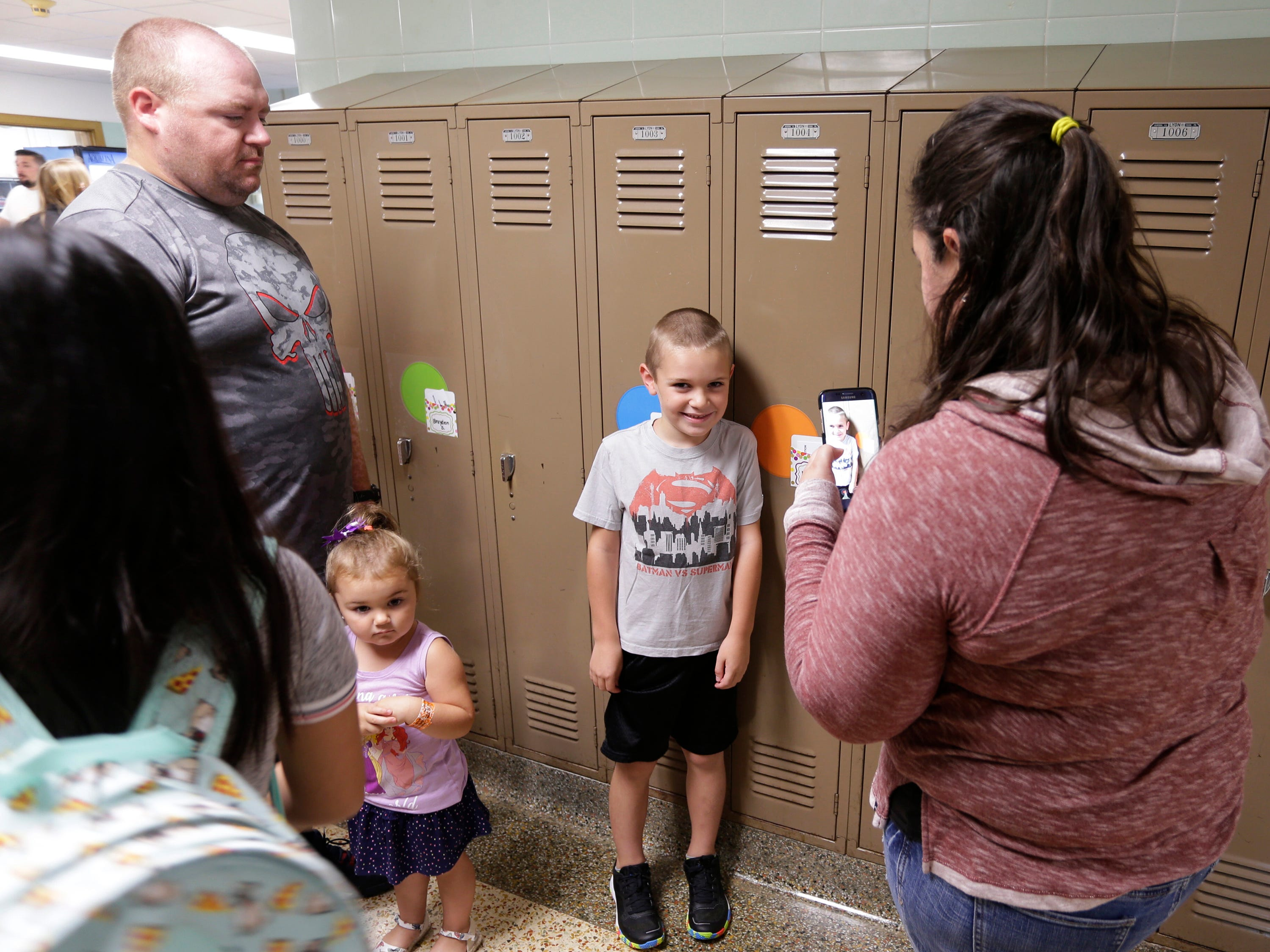 Nicole Graf, right, snaps a photo of her son Dylan, 6, center, while her husband Nate and daughter Brooklyn, 3, observes at Wilson Elementary School, Tuesday, September 4, 2018, in Sheboygan, Wis.  Dylan will be a first grader at the school that has seen many renovations during recent construction.