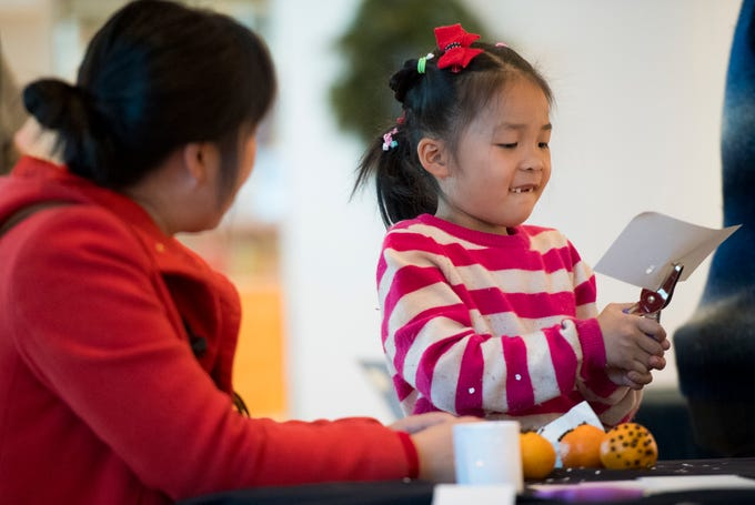 Elsa Li, 6, works hard to punch holes in her paper luminary during the Winter Solstice Celebration at the Southern Utah Museum of Art Friday, December 21, 2018. The event included crafts, live music, and storytelling.