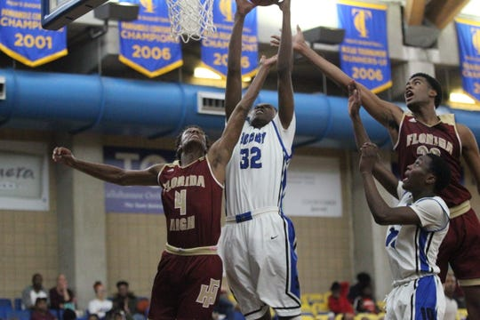 Godby center Autavian Gibson goes up for a rebound over Florida High's Willie Taggart Jr. (4) and Makai Willis during the 2018 Capital City Holiday Classic at TCC.