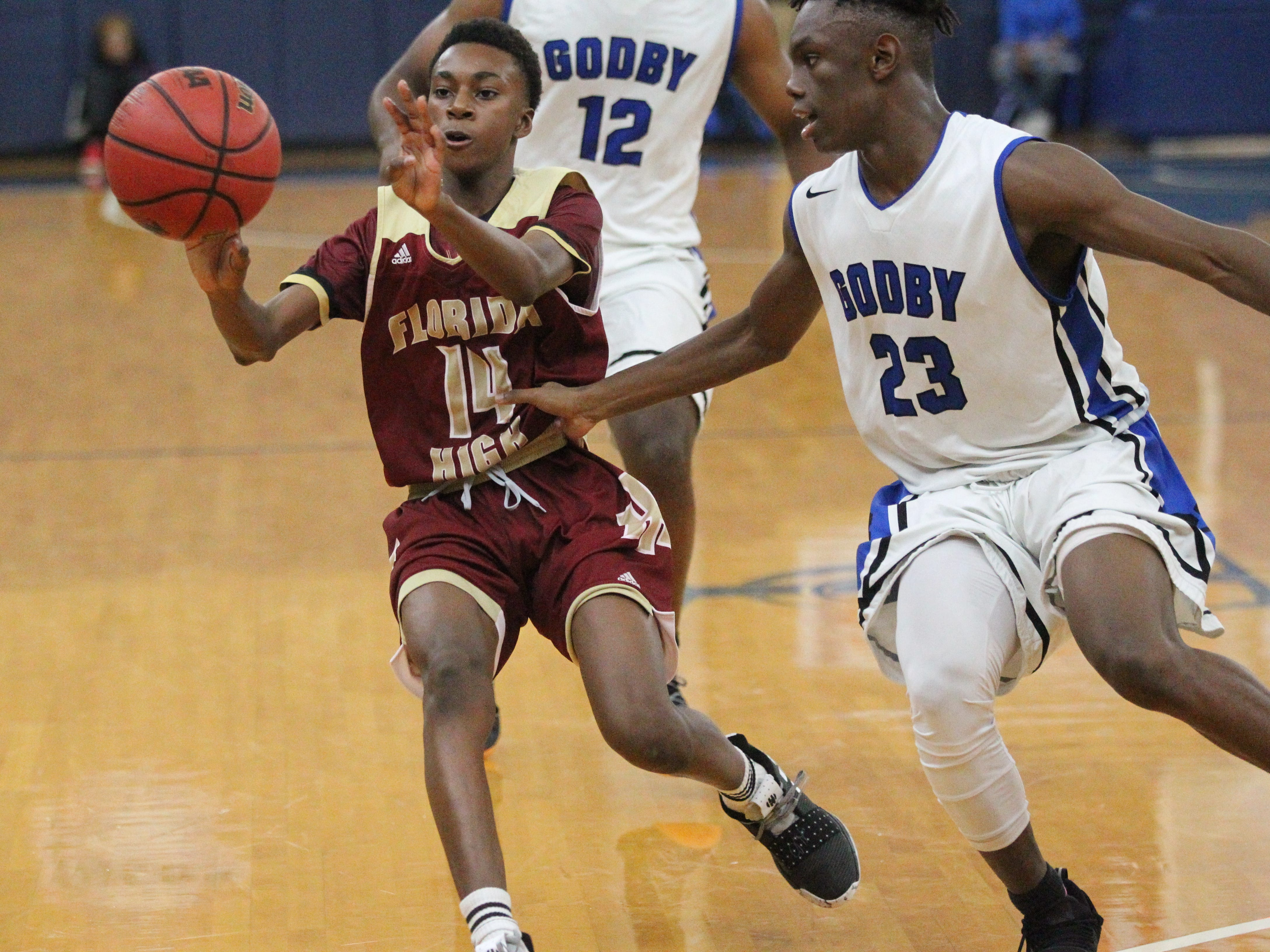 Florida High eighth-grader Anthony Robinson makes a pass to the corner as Godby's De'Shawn Rucker guards during the 2018 Capital City Holiday Classic at TCC.