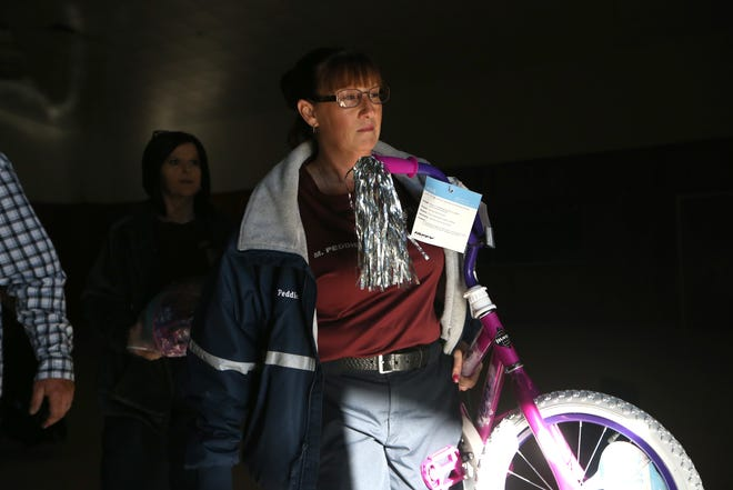 Melissa Peddie, founder of Love for Liberty, carries a a new pink bike for a little girl, as she leads volunteers with Love for Liberty, an organization that helps families impacted by Hurricane Michael by giving out toys and clothes for children, just in time for the holidays, Saturday, Dec. 22, 2018.