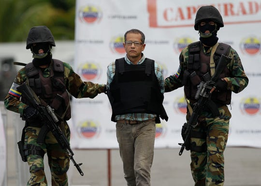 "In this Nov. 14, 2012, file photo, Colombian Jorge Cifuentes is escorted by National Guard officers during his deportation to Colombia from the Simon Bolivar airport in Maiquetia, near Caracas, Venezuela. Cifuentes, who once shipped Colombian cocaine to Joaquin ""El Chapo"" Guzman's Sinaloa cartel using airplanes made of carbon to deflect radar detection, is now one of the cooperating witnesses in the U.S. government's case against Mexican drug lord."