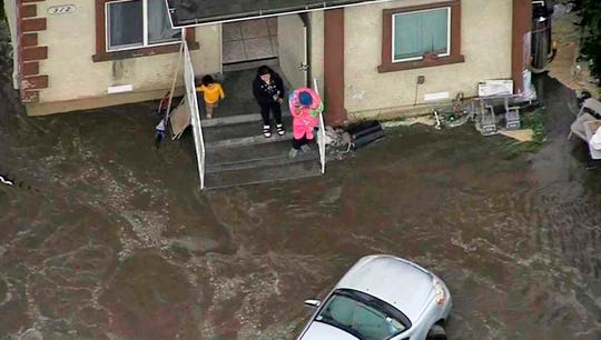 This photo from video provided by KNBC shows people stranded on the porch of a home on a street flooded by a predawn rupture of a water main in a Los Angeles neighborhood on Friday.