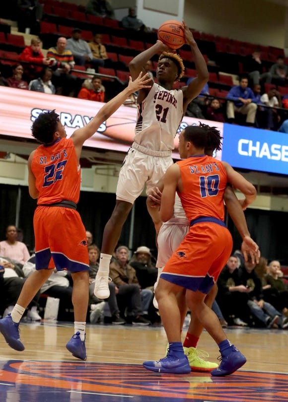 Adrian Griffin Jr. of Stepinac shoots over Justin Hayes and Tahron Allen of St. Raymond during a Slam Dunk Basketball Tournament game at the Westchester County Center in White Plains Dec. 21. 2018. St. Raymond defeated Stepinac in overtime 72-69.