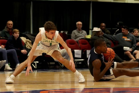 Clevmer Lubin of Suffern beats Brant Steinberg of Irvington to the loose ball during a Slam Dunk Basketball Tournament challenge game at the Westchester County Center in White Plains Dec. 22. 2018. Suffern defeated Irvington 48-35.