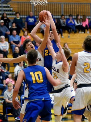 West Muskingum's Koltin Olney is met in the lane by Philo's Cody Butler, left, and Austen Bonifant during the Electrics' 48-31 win on Friday at The Power Plant.