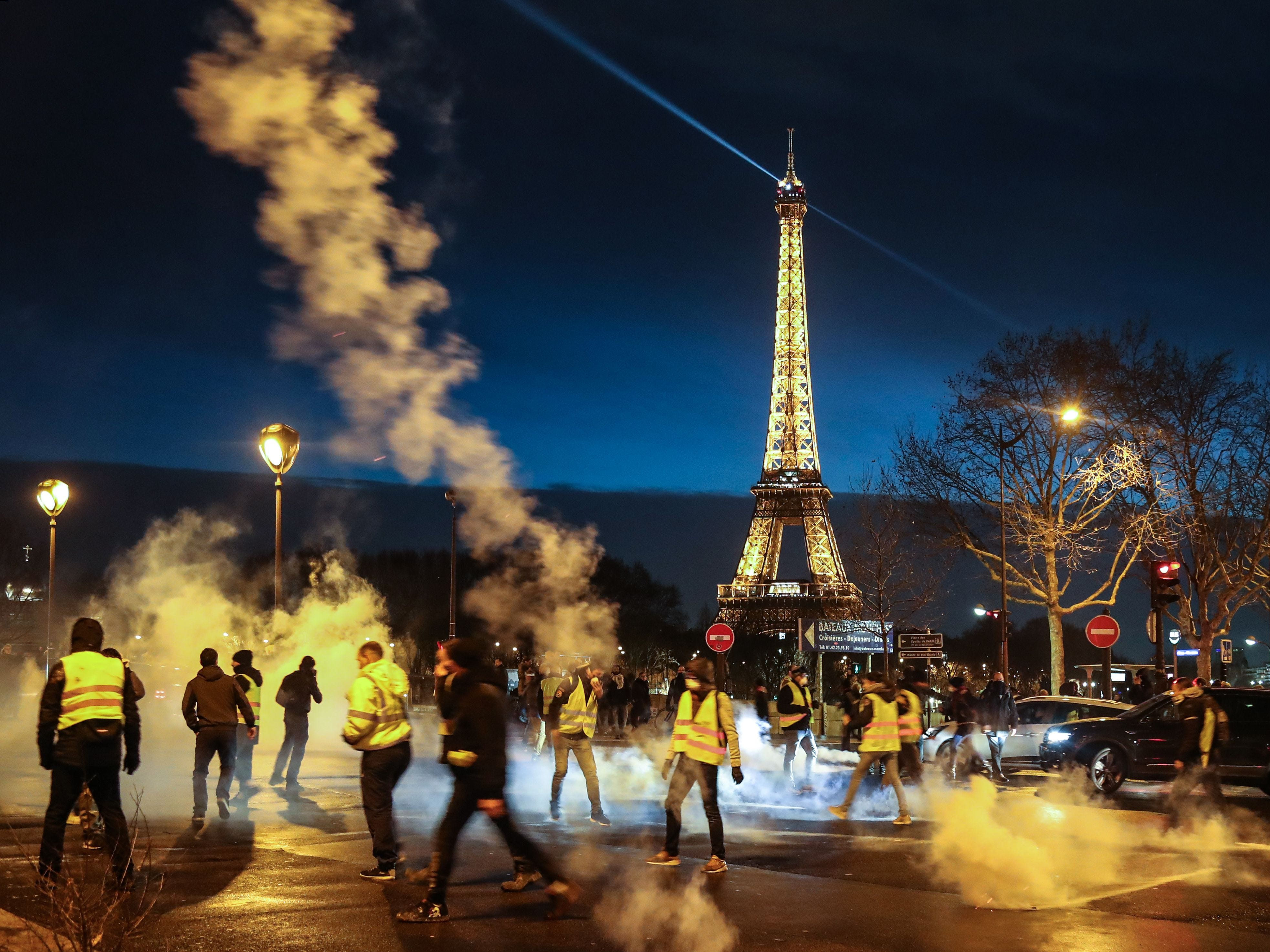 "Demonstrators of the French ""yellow vests""  throws tear gas canisters back as police disperse the end of a protest in central Paris on Dec. 22, 2018 as the movement turned out in small numbers for a sixth Saturday of nationwide demonstrations.  In Paris, the scene of violent clashes in previous demonstrations, traffic was normal in the morning and most shops, except for some luxury boutiques, were open for business in the busy weekend before Christmas."