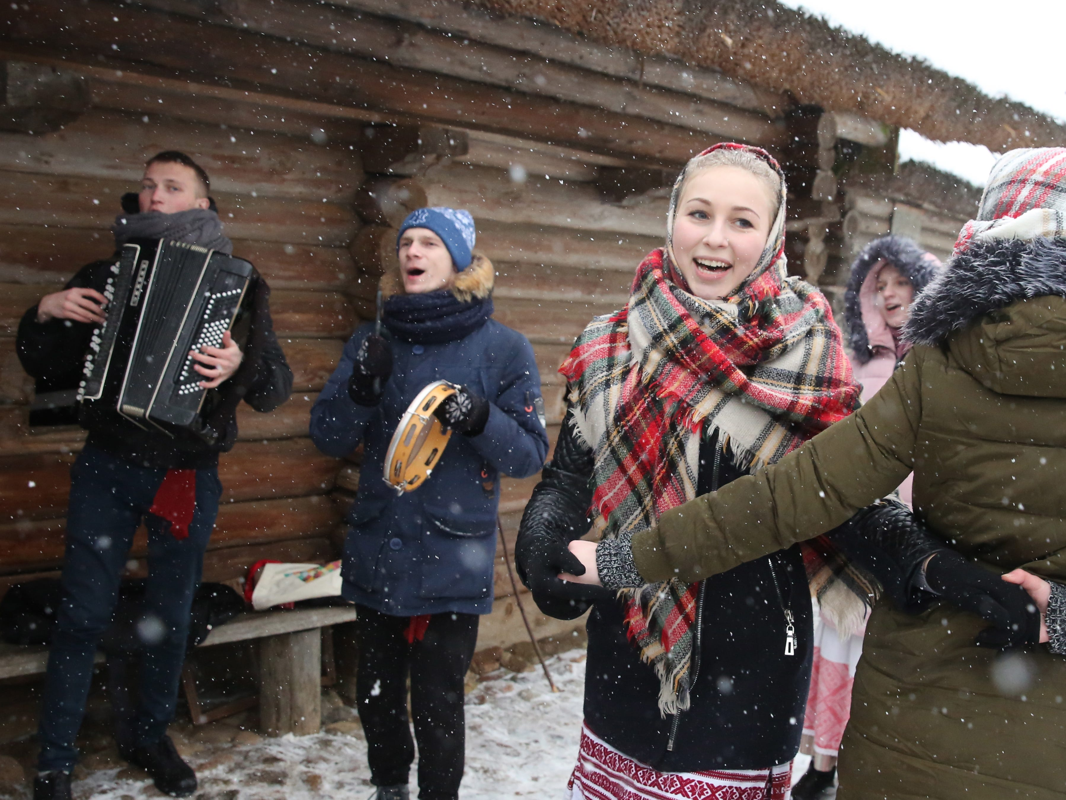 Belarussian artists wearing traditional costumes sing carol songs and dance during Koliady celebrations in the village of Ozertso.
