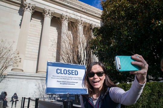 Jamie Parrish, from Minneapolis, takes a selfie in front of the closed sign at the National Archives, Saturday, Dec. 22, 2018 in Washington. The House and Senate are gaveling back in for a rare weekend session amid a partial government shutdown over President Donald Trump's demand for billions of dollars for a border wall.