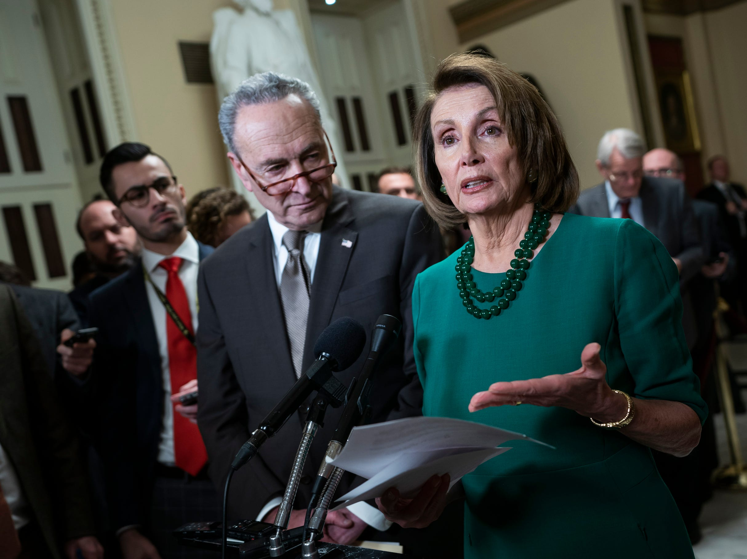 Democratic House Minority Leader Nancy Pelosi (R) and Democratic Senate Minority Leader Chuck Schumer (C) speak to the media, Thursday, as lawmakers prepare to vote on a new budget resolution to avert a government shutdown.