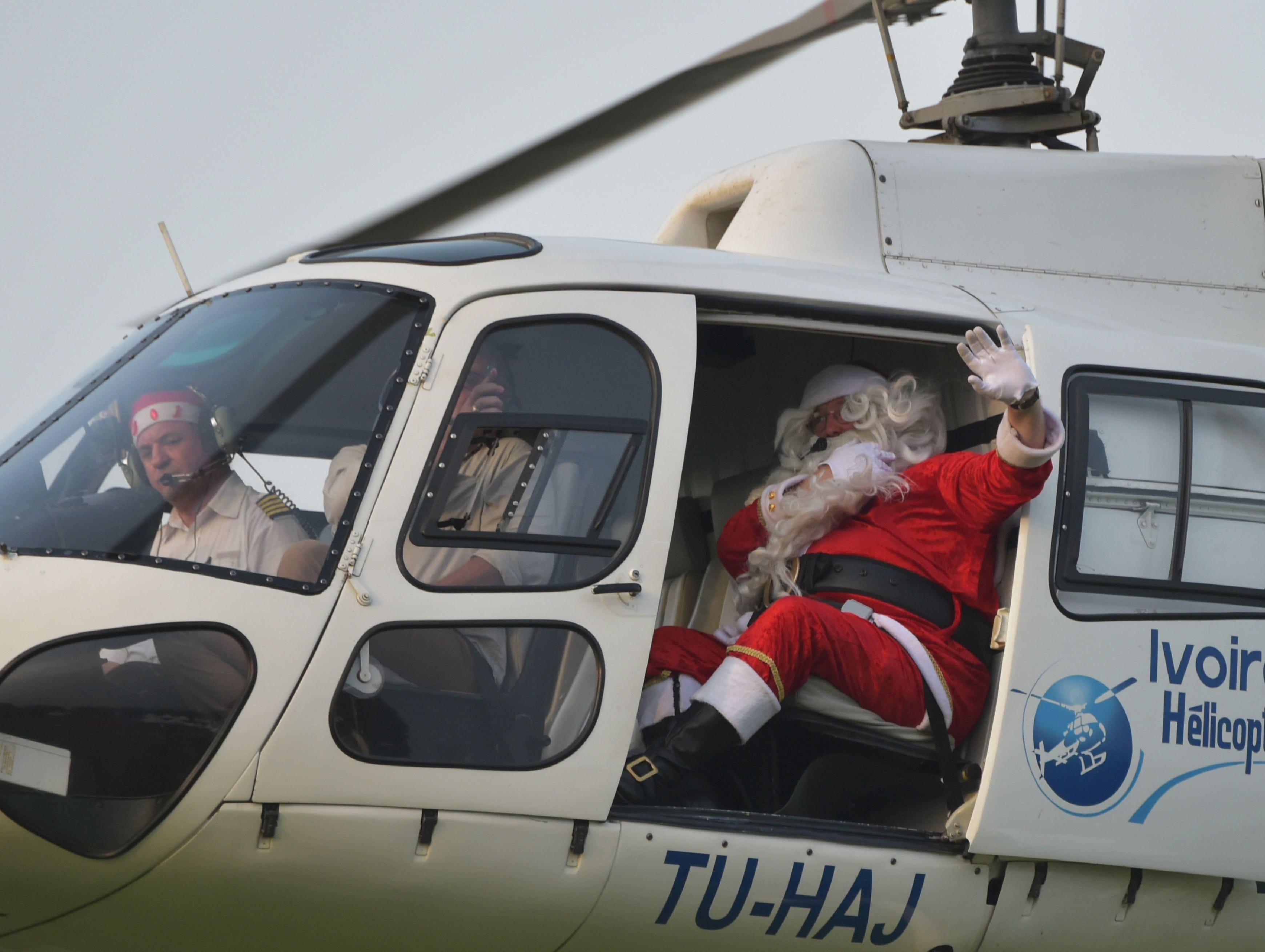 A man dressed as Santa Claus wave from a helicopter as he arrives at the presidential palace in Abidjan on Dec. 22, 2018, during a Christmas event organized by the Children of Africa Foundation.