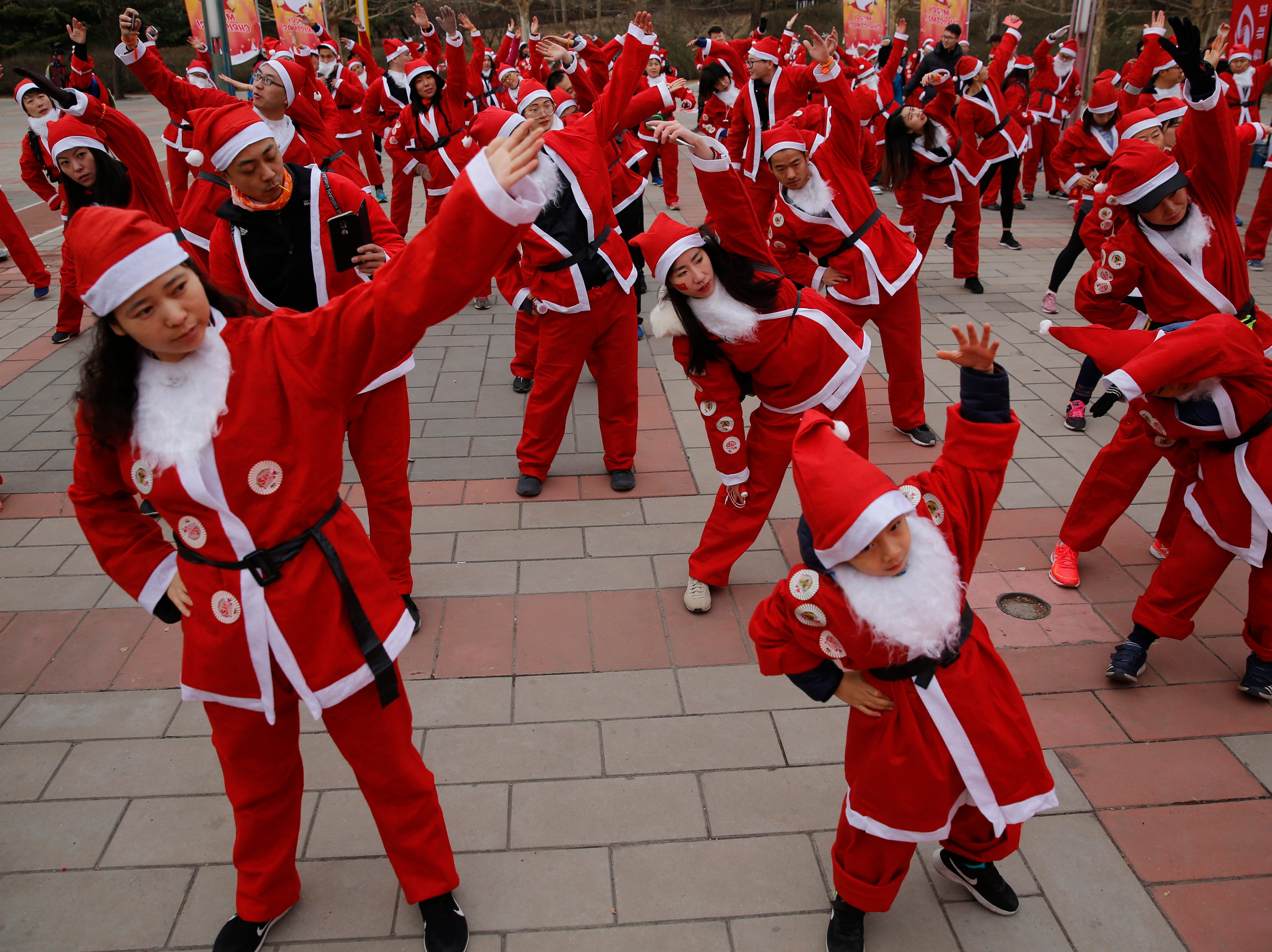 Chinese participants dressed in Santa Claus costumes warm up prior to the start of a Santa Claus fun run event to celebrate the upcoming Christmas Day at Chaoyang park in Beijing, China on Dec. 22, 2018.