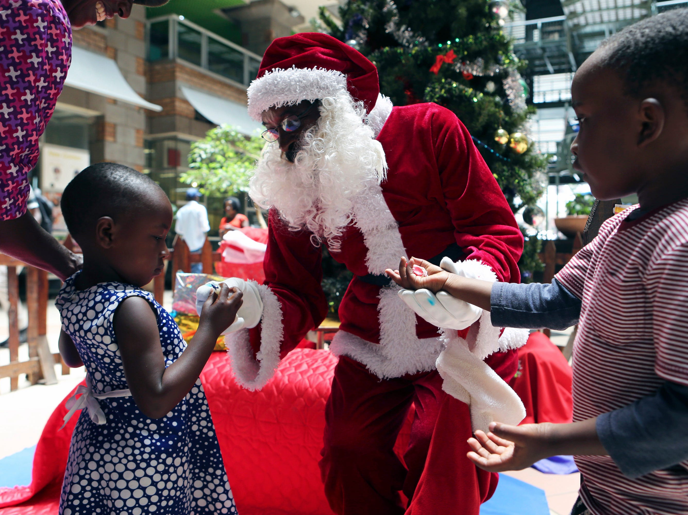 Santa Claus gives sweets to children at a shopping mall in Harare on Dec, 21, 2018. The Christmas lights are up in Zimbabwe's capital but the mood is less than festive as the country grapples with an economic crisis that prevents many families from enjoying the holiday season. Zimbabwe is experiencing its worst economic meltdown in a decade.