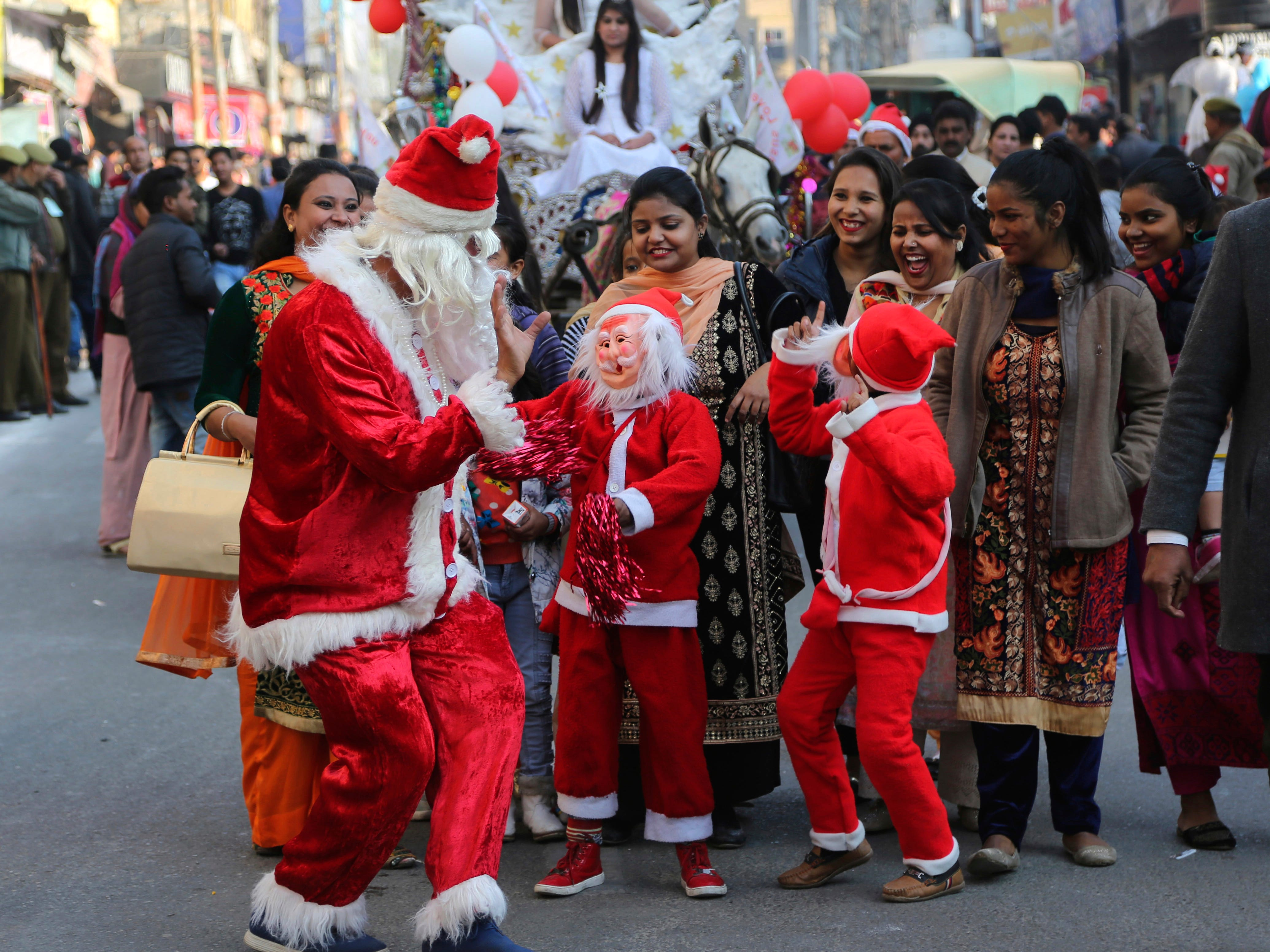 An Indian man and children dressed as Santa dance to participate in a procession to celebrate Christmas in Jammu, India, Saturday, Dec. 22, 2018. Though Christians make up only about 2 percent of India's 1 billion-plus population, Christmas is a national holiday celebrated with much fanfare.