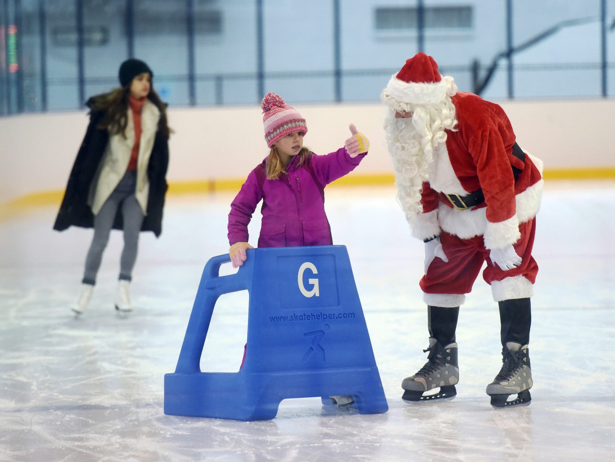 Santa Claus, played by Carmeron Robertson, talks with Ella Westerbeek, 6, while ice skating Saturday, Dec. 22, 2018, at the John & Dede Howard Ice Arena in St. Joseph, Mich.