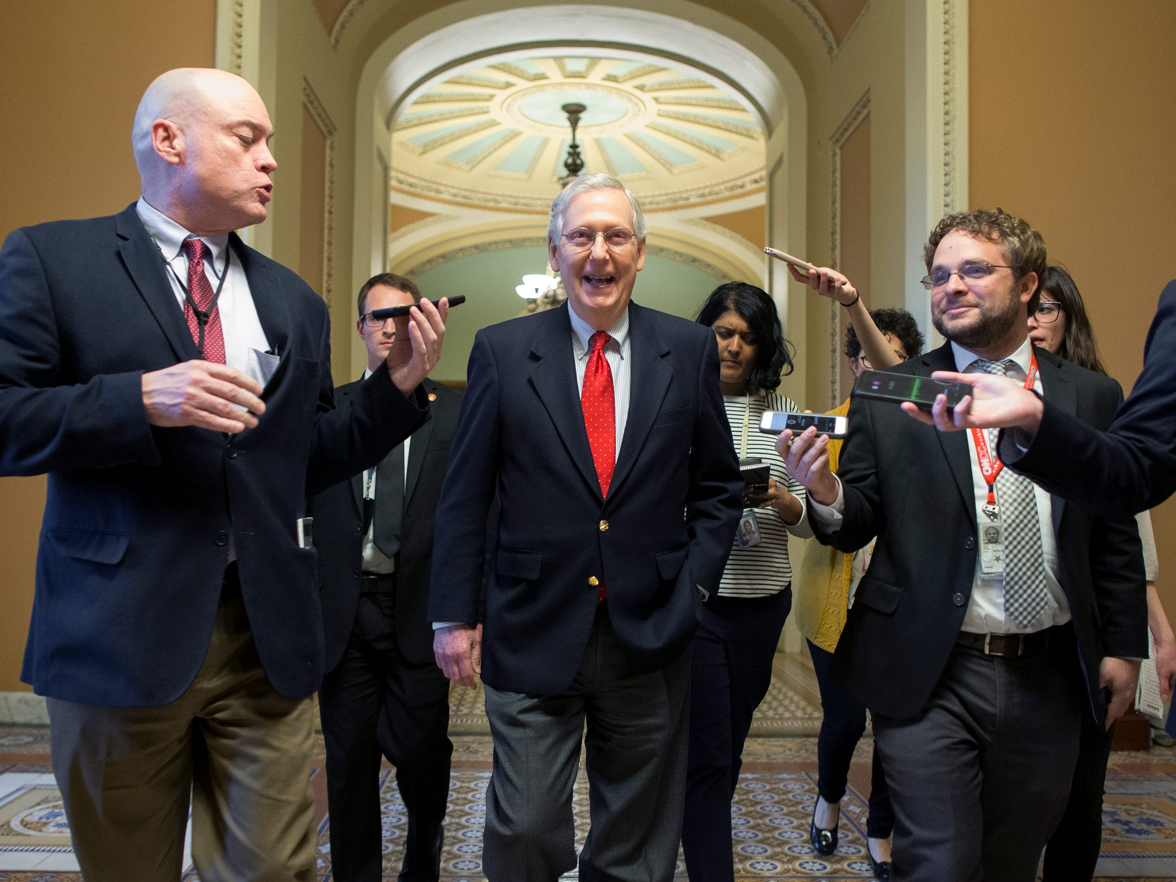 Senate Majority Leader Republican Mitch McConnell, center, is followed by members of the news media as he walks from the Senate floor on Capitol Hill in Washington, DC, on Dec. 21, 2018. President Trump rejected a continuing resolution to fund the federal government through Feb. 8, 2019, threatening a partial shutdown unless funding is included for his border wall.