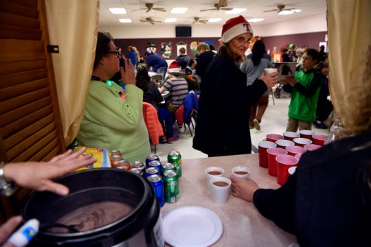 Visitors drink free hot chocolate and eat pizza at the Tye Community Center, following the city's second-annual Christmas parade.