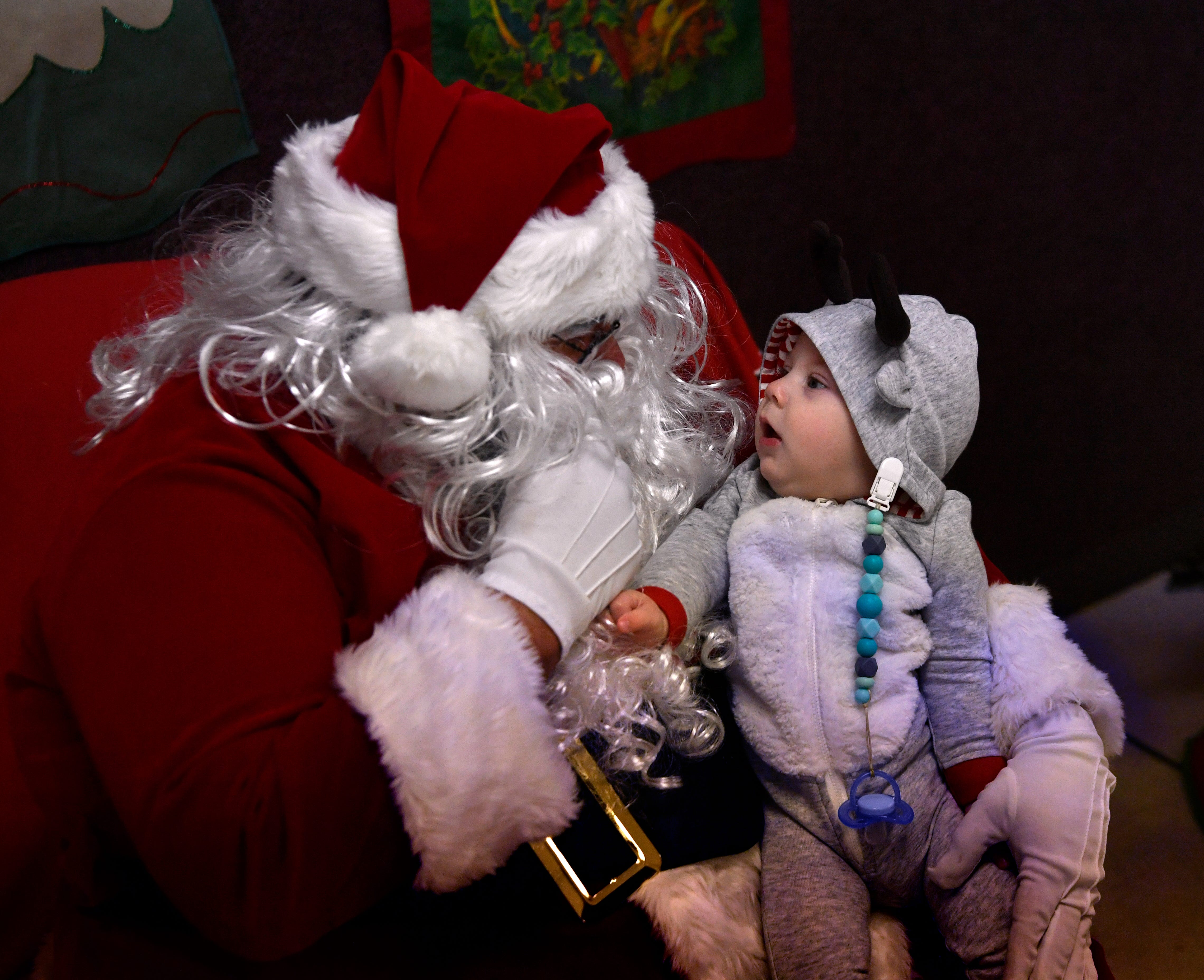 Carson Barriere, 6 months, grabs a fistful of Santa's beard as he gets a closer view Thursday. After the Christmas parade, spectators moved to the Tye Community Center for time with Santa, a gift, hot chocolate and pizza.