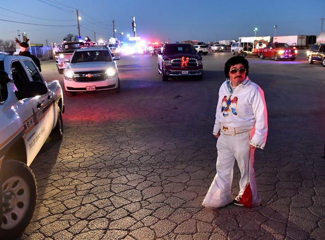 Dressed as Elvis Presley, James Gober waits for the start of Tye's second-annual Christmas parade Thursday.