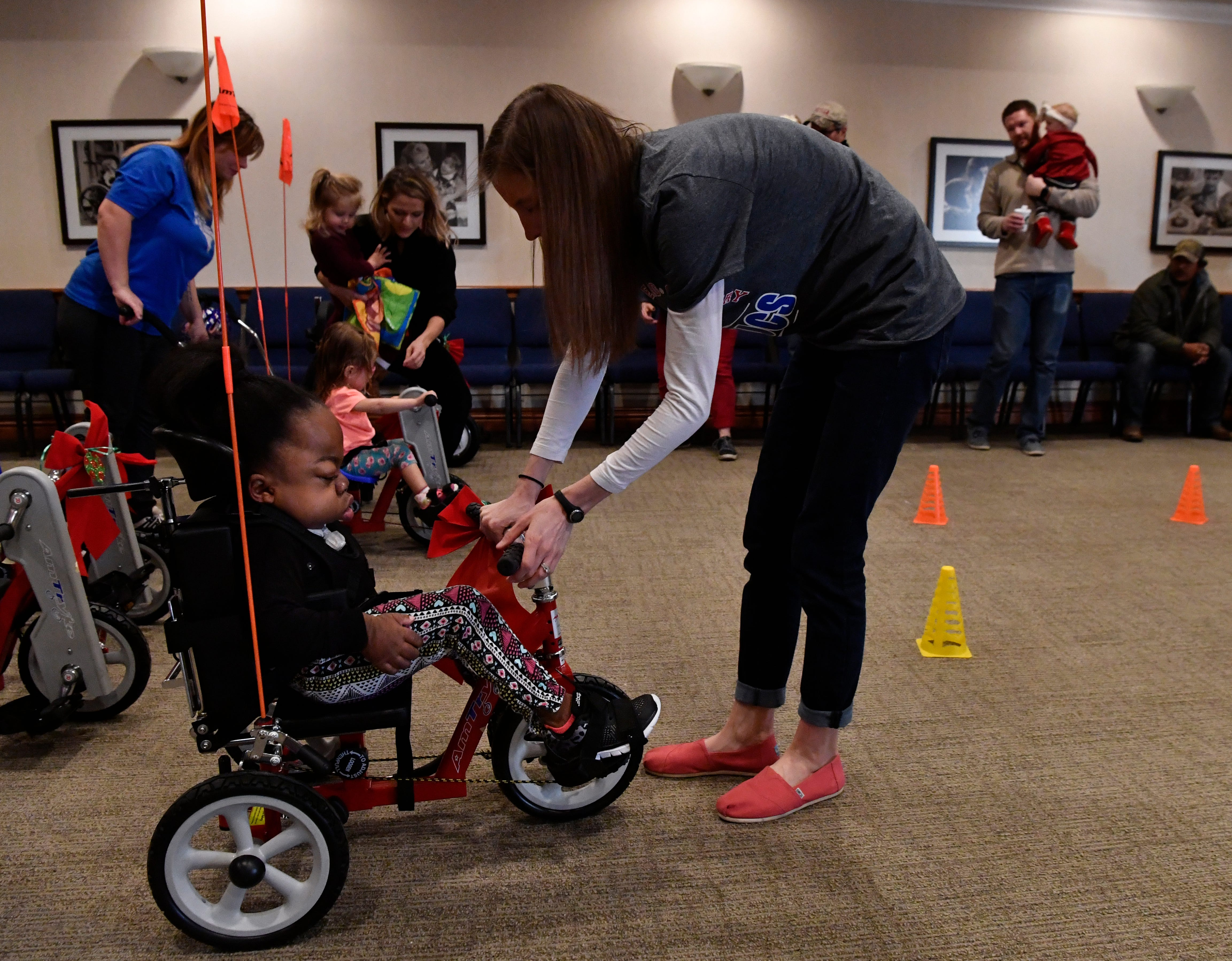 Sara Snowden assists Kiara Walker, 13, with her new adaptive tricycle Saturday at the West Texas Rehabilitation Center. The Abilene Big Country AMBUCS club provided 12 trikes Saturday to area children.