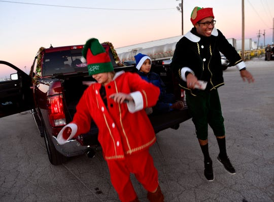Karly Hohhertz (left) and Chris Wilson jump off a tailgate after arriving at the staging area for the Tye Christmas parade Thursday. This was the city's second holiday parade.