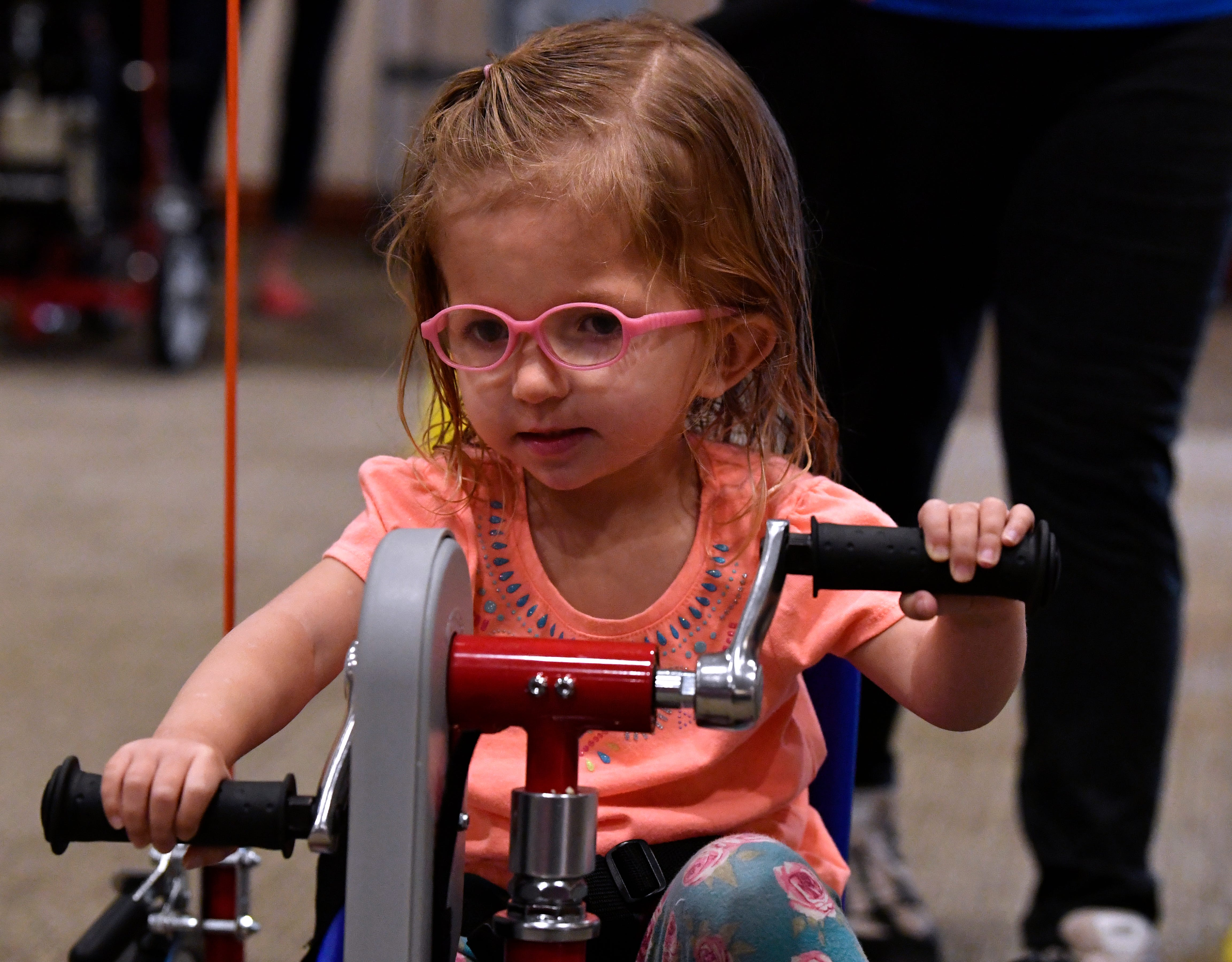 Ivory Bass, 3, uses hand cranks and pedals simultaneously as she wheels around the West Texas Rehabilitation Center board room Saturday.
