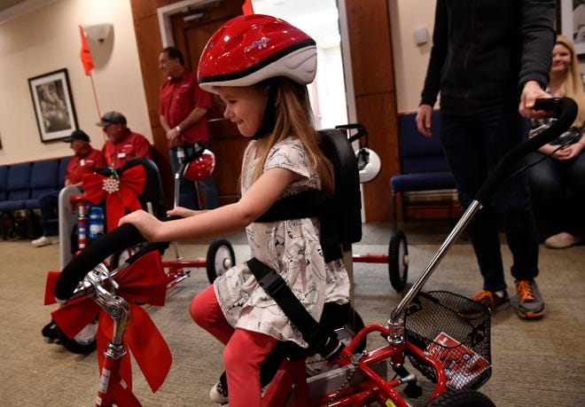 Elsa Cooper pedals her new Amtryke Saturday at West Texas Rehabilitation Center. The adaptive tricycle will enable Elsa to strengthen muscles so that one day she might ride a standard bicycle. The Abilene Big Country AMBUCS club provided 12 trikes Saturday to area children.