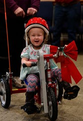 NataLee Bomar, 3, laughs as her grandmother Samantha Beaty helps her pedal around the board room of the West Texas Rehabilitation Center Saturday.