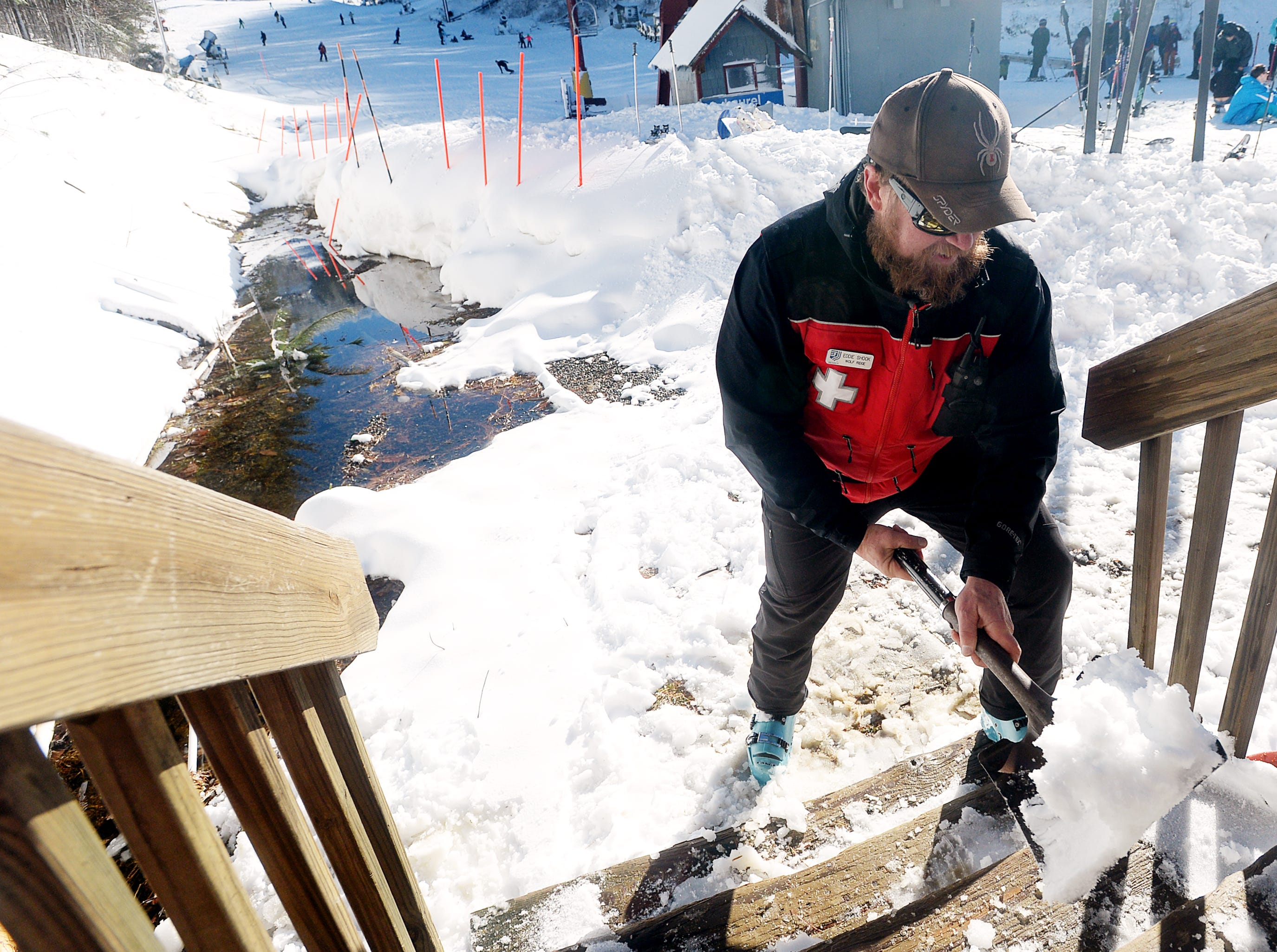 "Eddie Shook, a second-year Ski Patrol member, shovels the stairs at the Ski Patrol headquarters at Wolf Ridge Ski Resort in Mars Hill Dec. 22, 2018. ""Shoveling is a good thing,"" said Shook of the fresh snow at the resort."